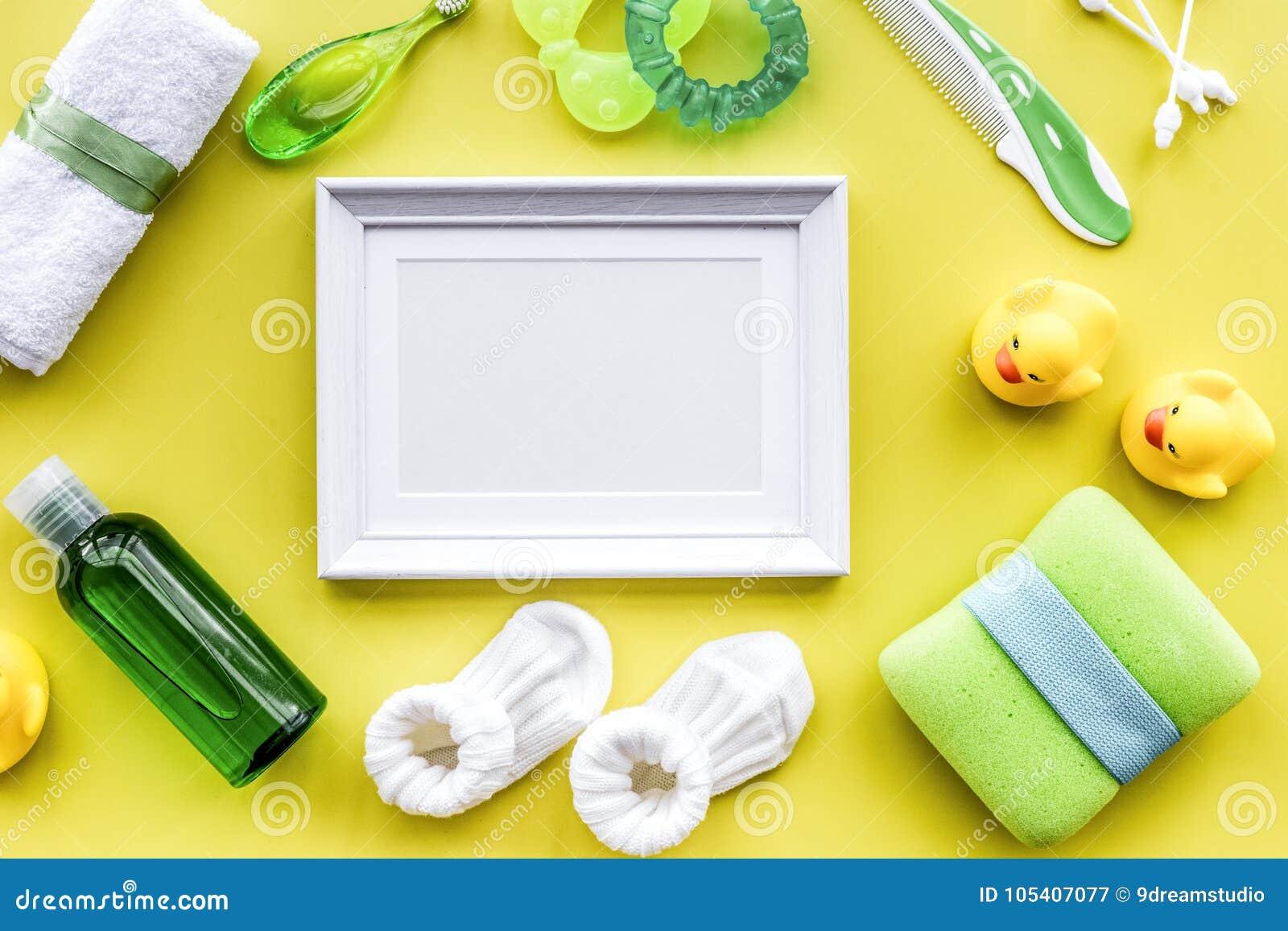 Accesorios del bebé para el baño con el cosmético, el marco y los patos del cuerpo encendido