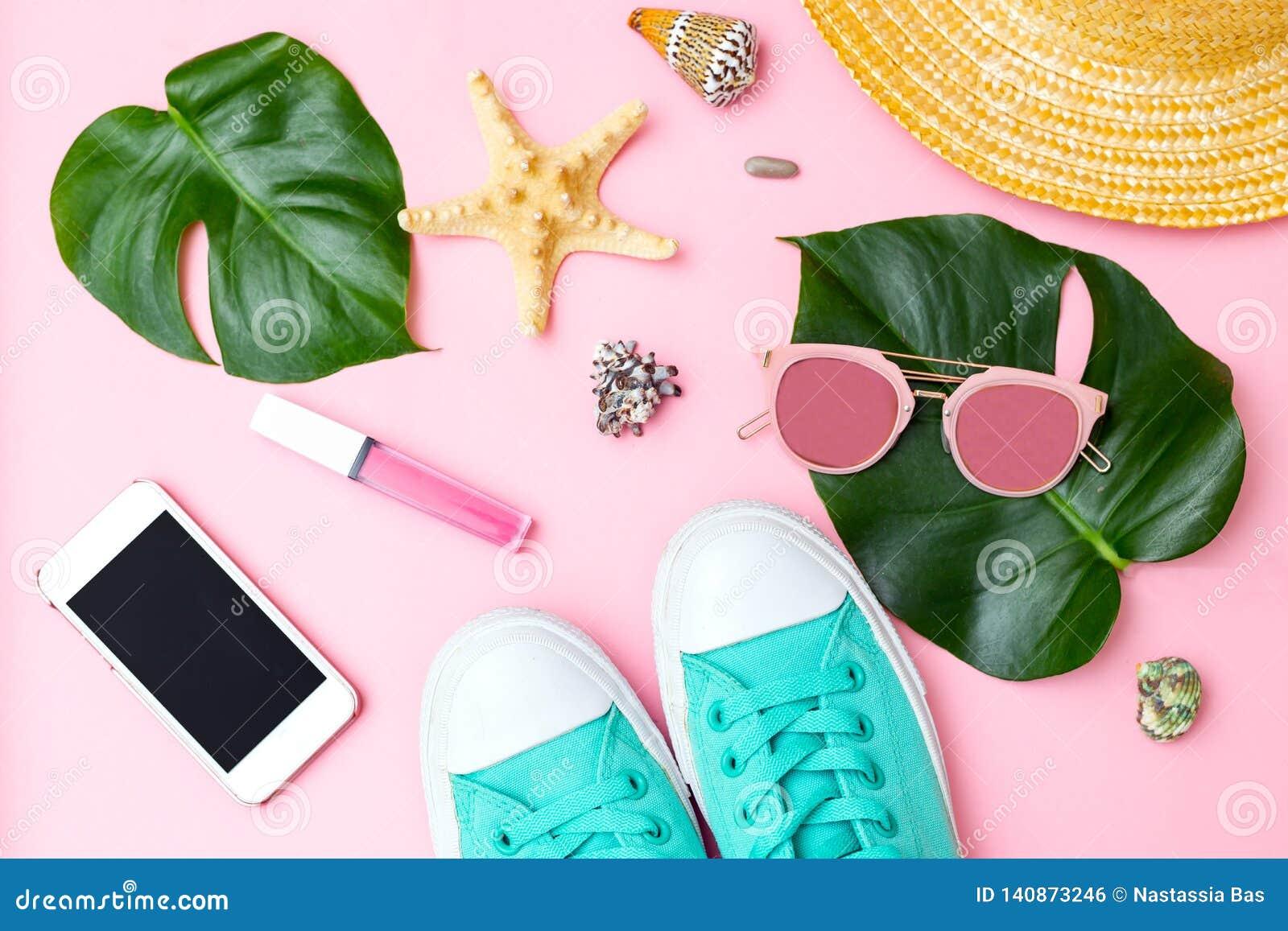 Accesorios femeninos del verano y del viaje en fondo rosado Endecha plana
