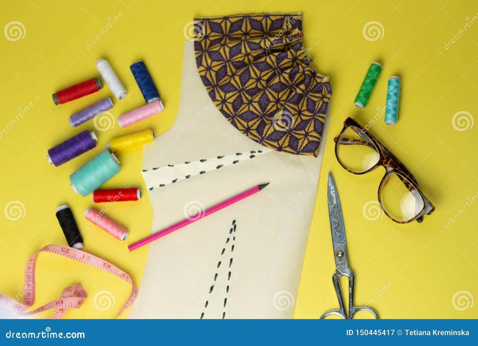 Accesorios y tela de costura en un fondo del yelow Hilos de coser, pernos, modelo y centímetro de costura Para coser en casa tapa