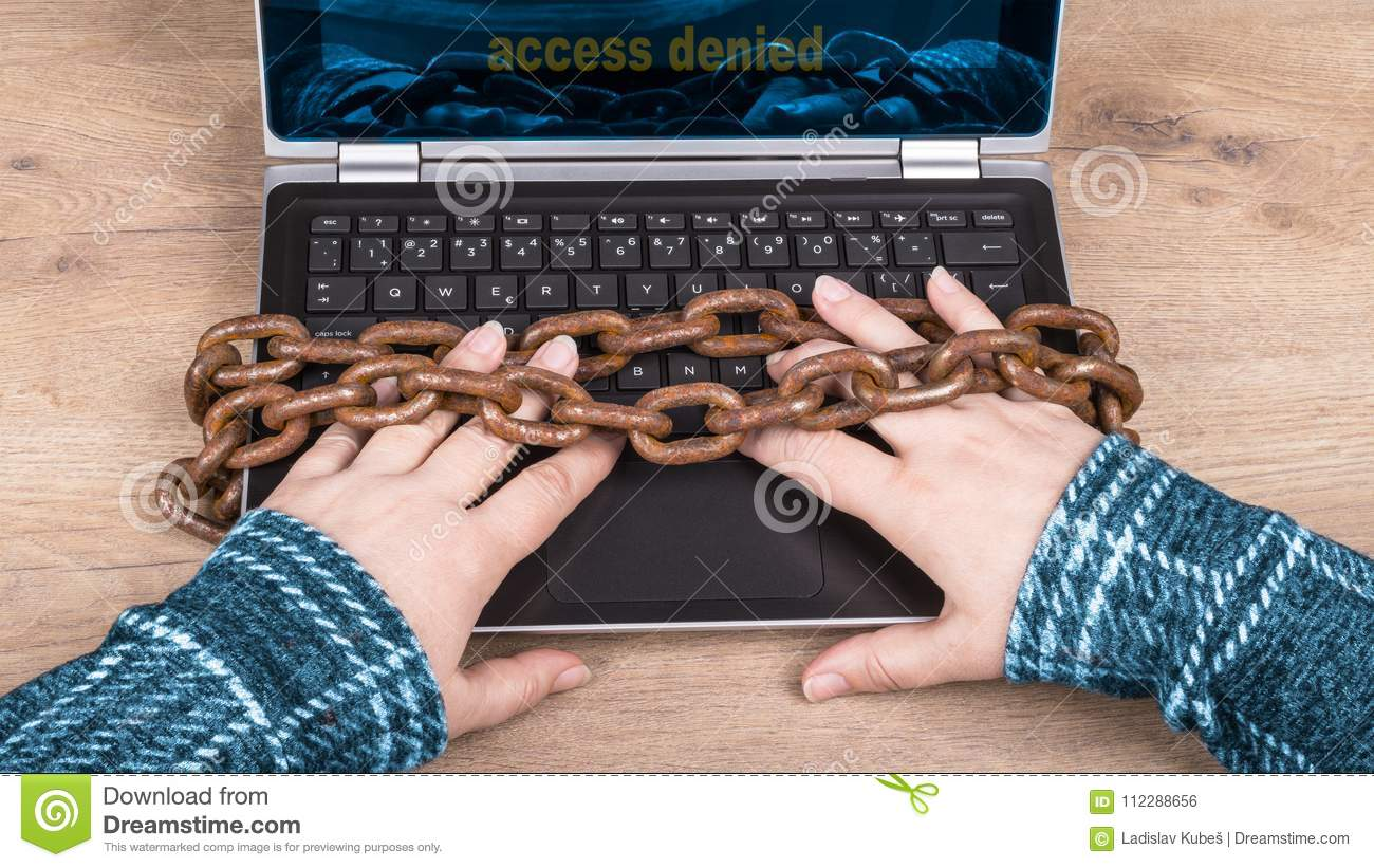 Close-up of hands, laptop keyboard and old rusty chains on wood background