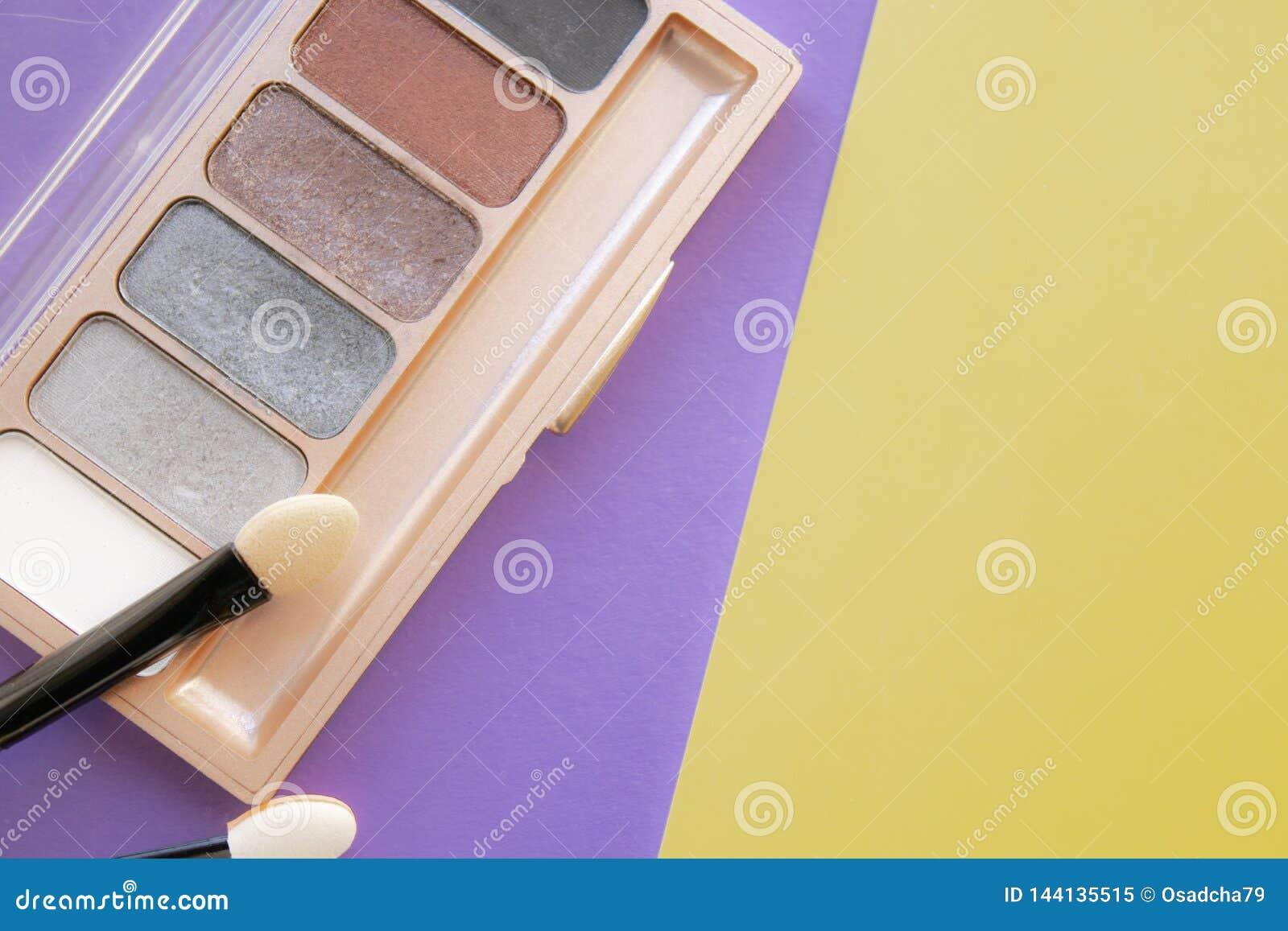 Accessoires cosmétiques Une brosse, fard à paupières sur un jaune, fond pourpre
