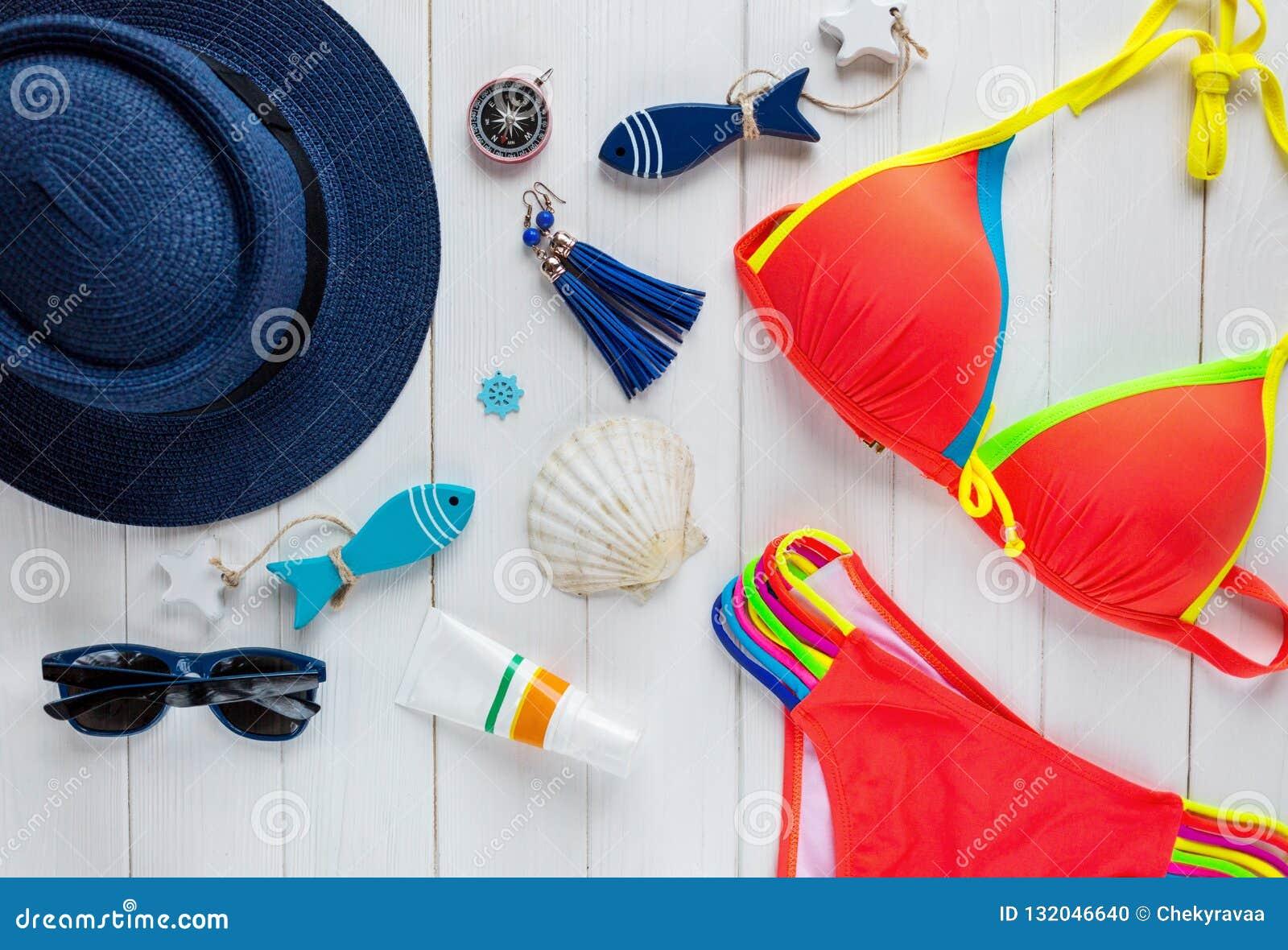 Accessoires d été pour des vacances : chapeau de paille, boussole, coquilles, boucles d oreille, maillot de bain, verres de solei