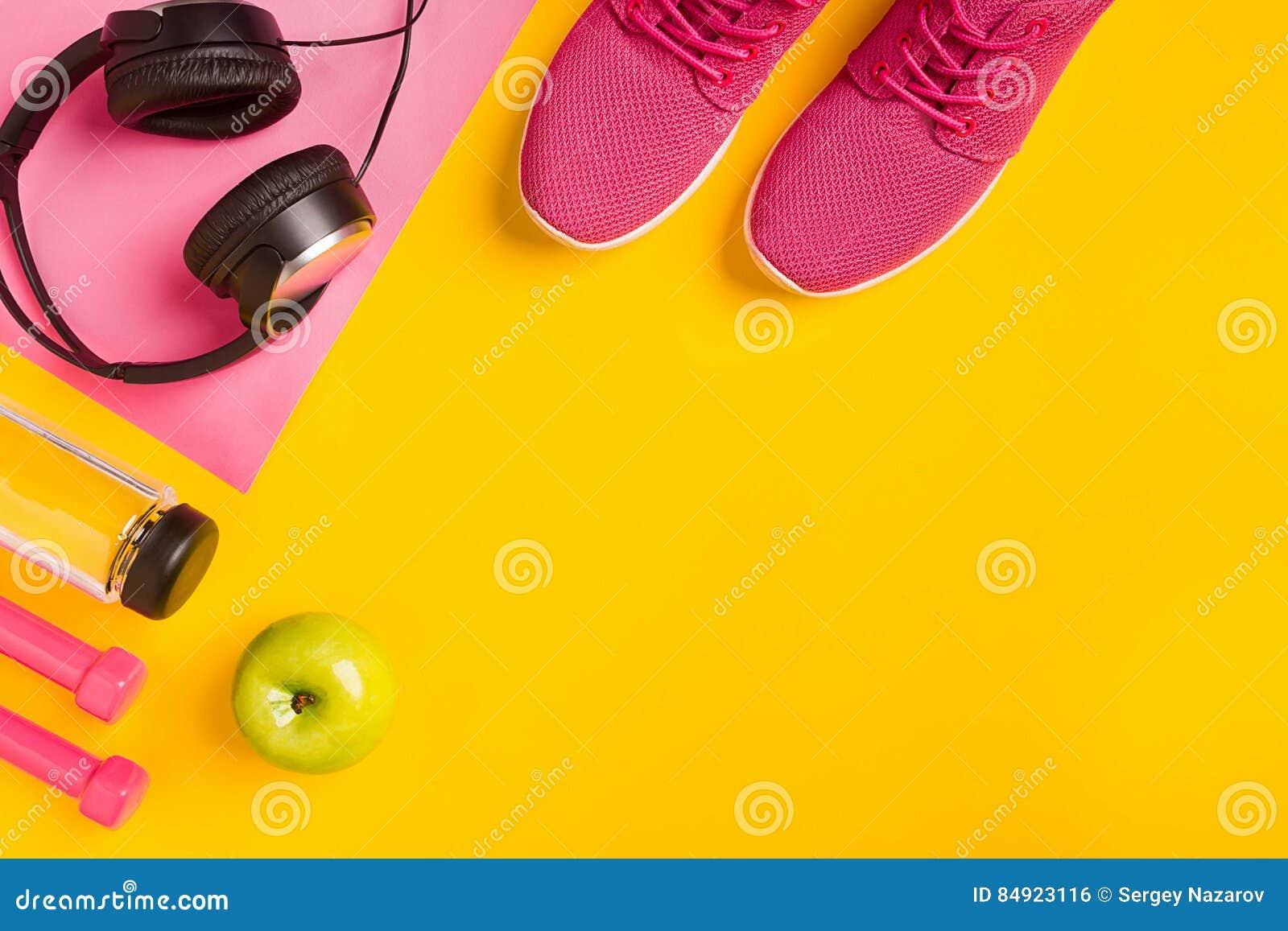 Accessoires de forme physique sur un fond jaune Espadrilles, bouteille de l eau, écouteurs et haltères