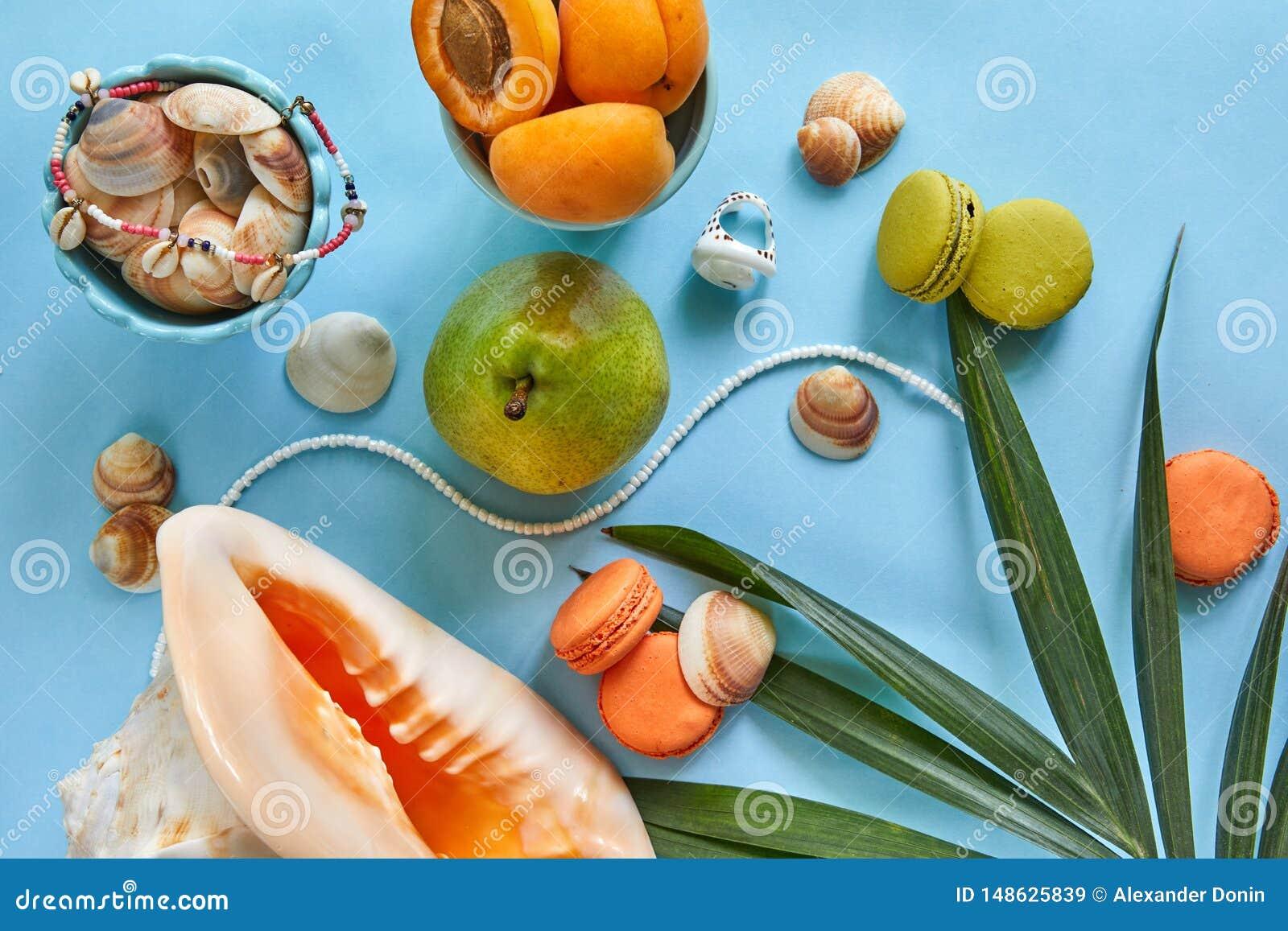 Accessoires de plage, fruits savoureux frais et macaron sur un fond bleu