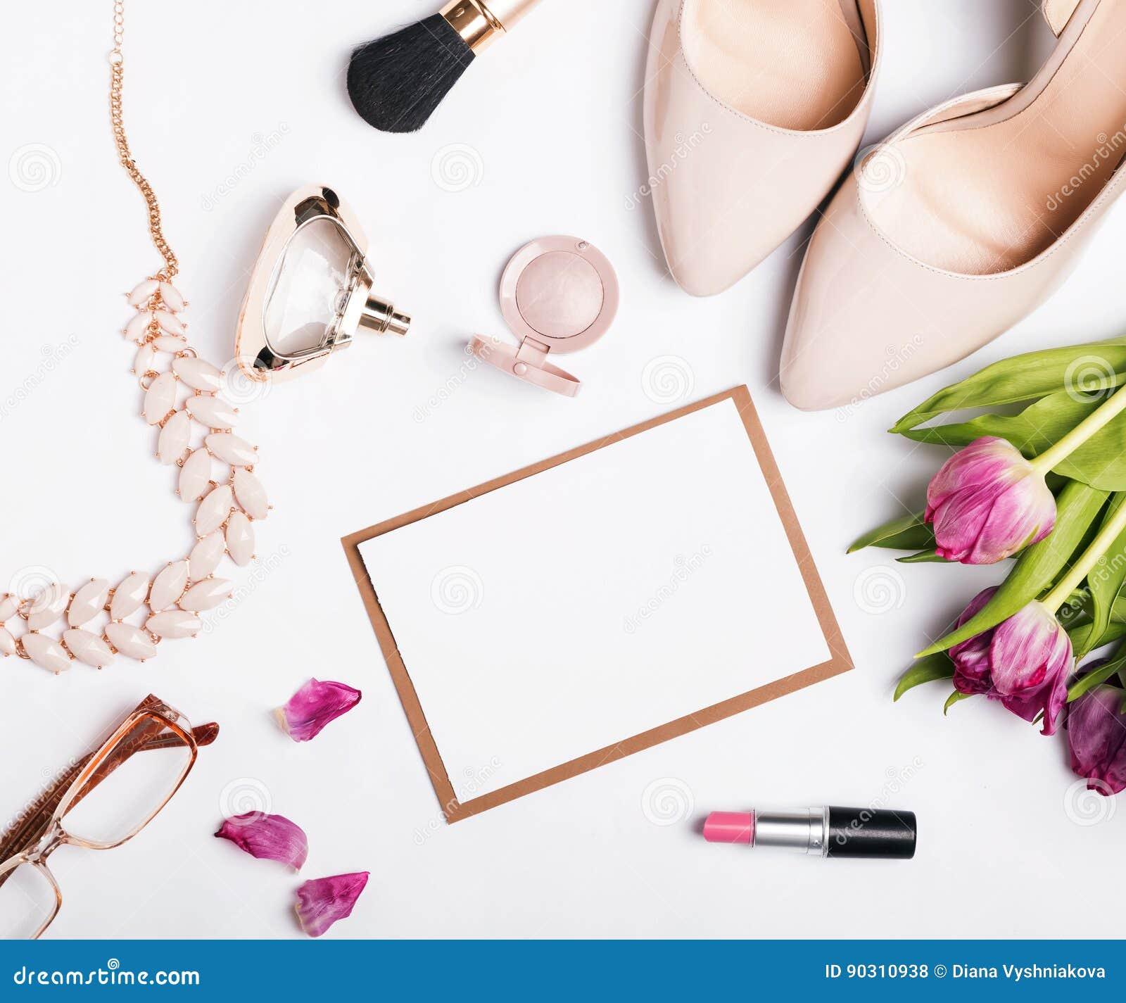 Accessoires du ` s de femme de couleur beige, des tulipes roses et du papier blanc