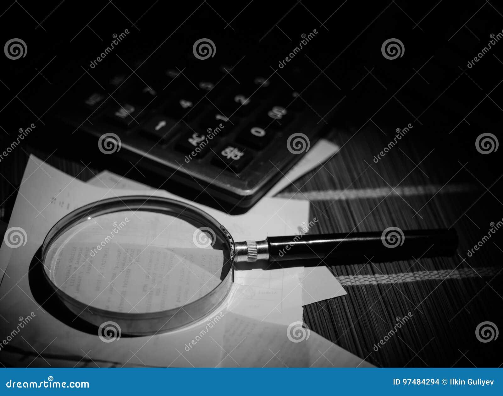 Accessori di affari (lente, calcolatore) e grafici, tavole, grafici su una tavola con fondo scuro Fuoco selettivo