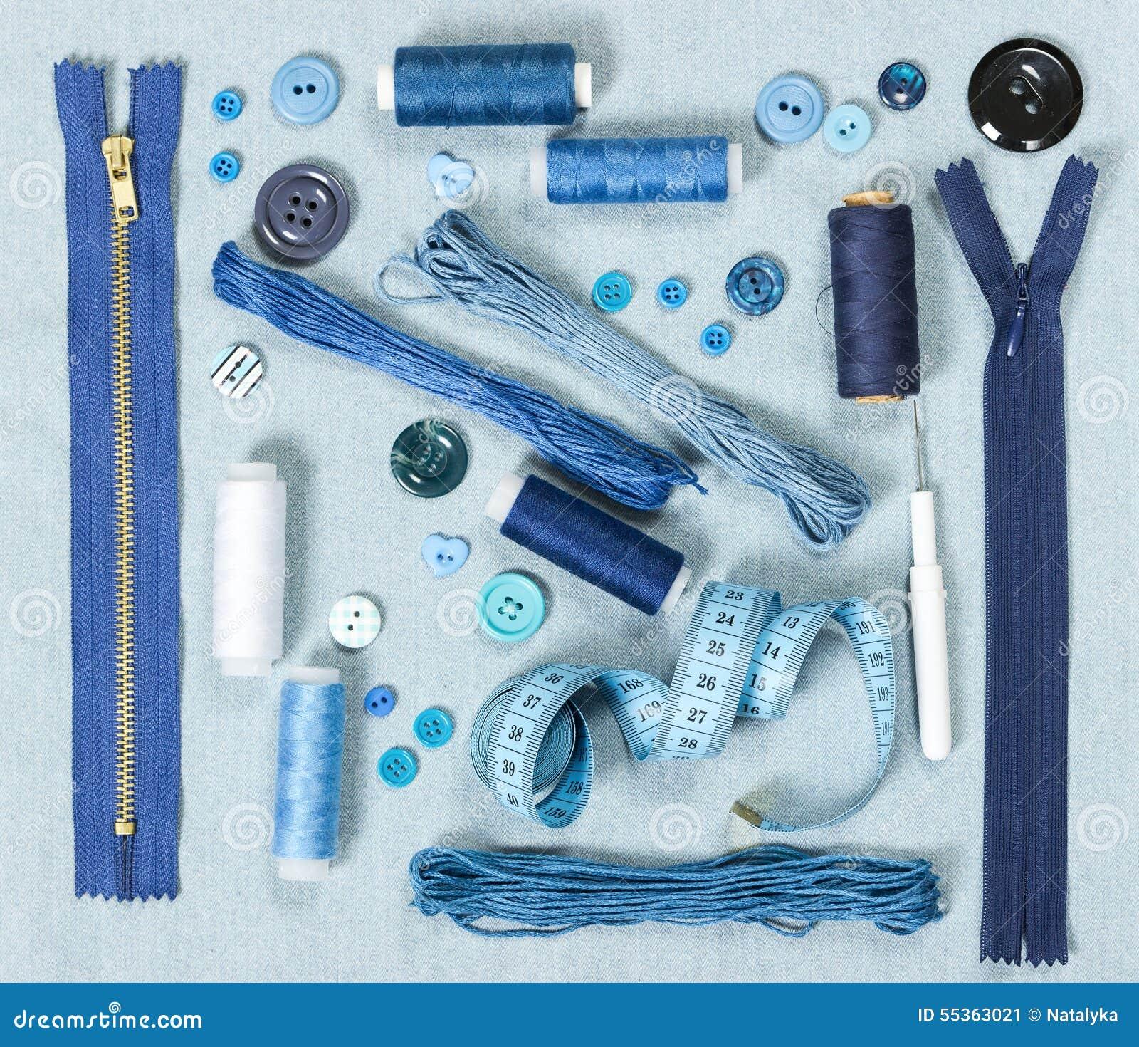 Accessori di cucito sul fondo blu del denim