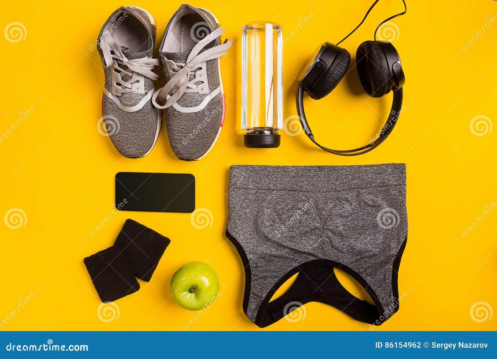Accessori di forma fisica su fondo giallo Le scarpe da tennis, la bottiglia dell acqua, le cuffie e lo sport completano