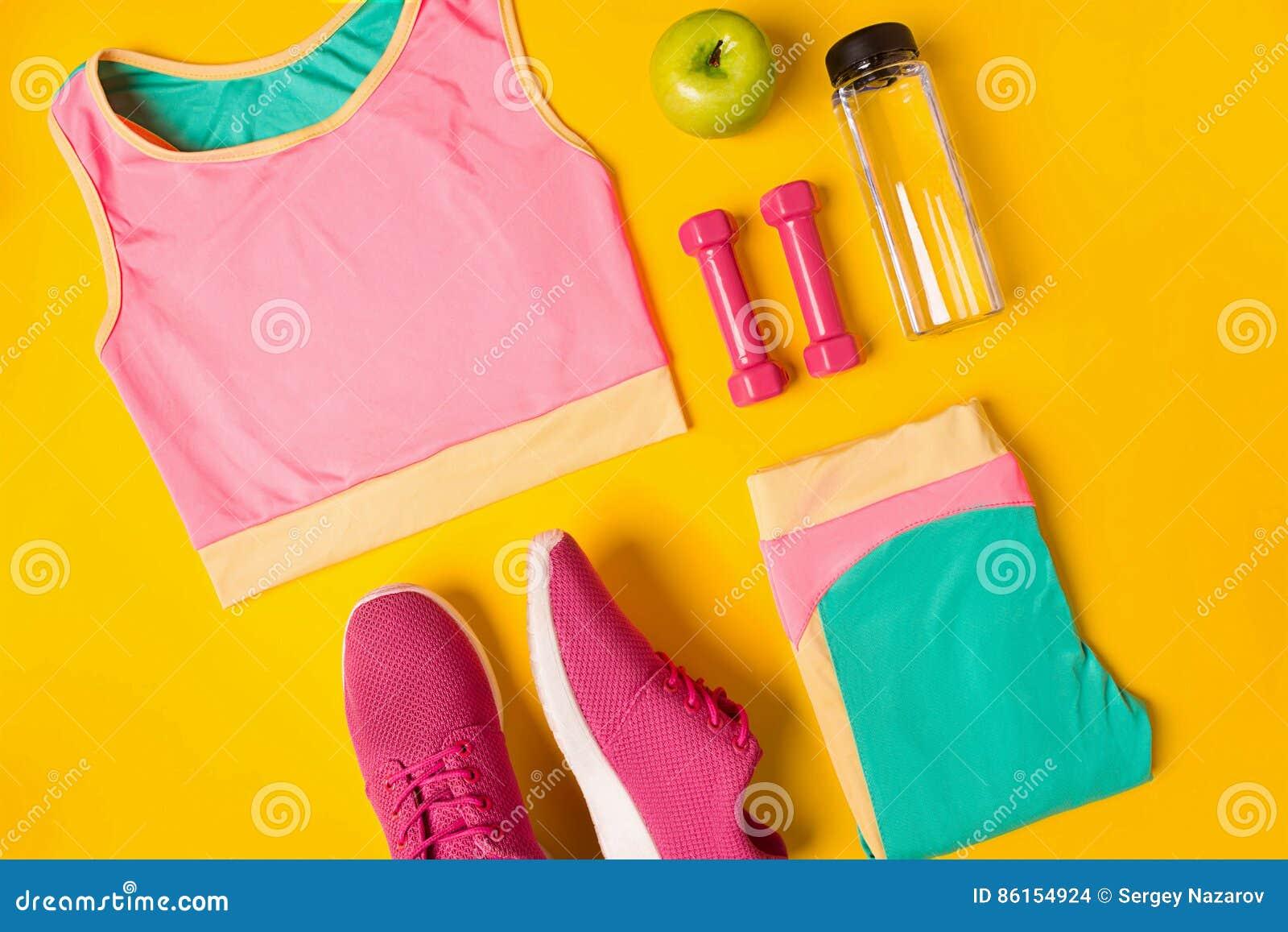 Accessori di forma fisica su fondo giallo Le scarpe da tennis, la bottiglia dell acqua, le teste di legno e lo sport completano