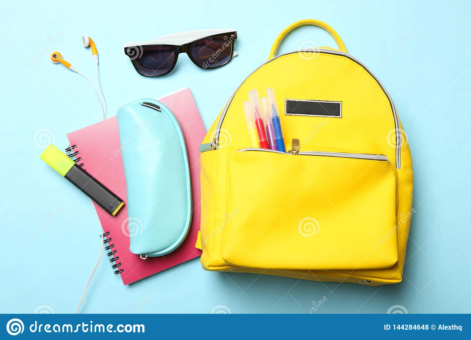 Yellow backpack with different school supplies and accessories
