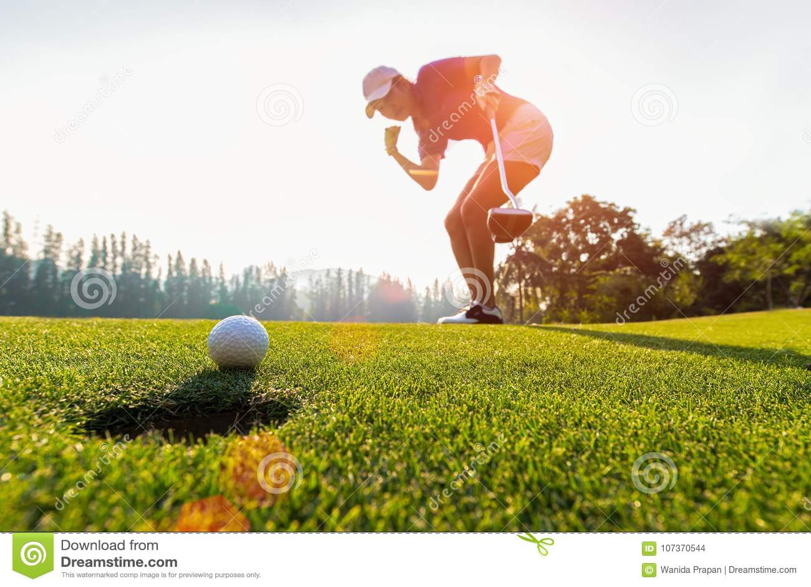 Acción asiática del golfista de la mujer a ganar después de la pelota de golf que pone larga en el golf verde, tiempo de la puest