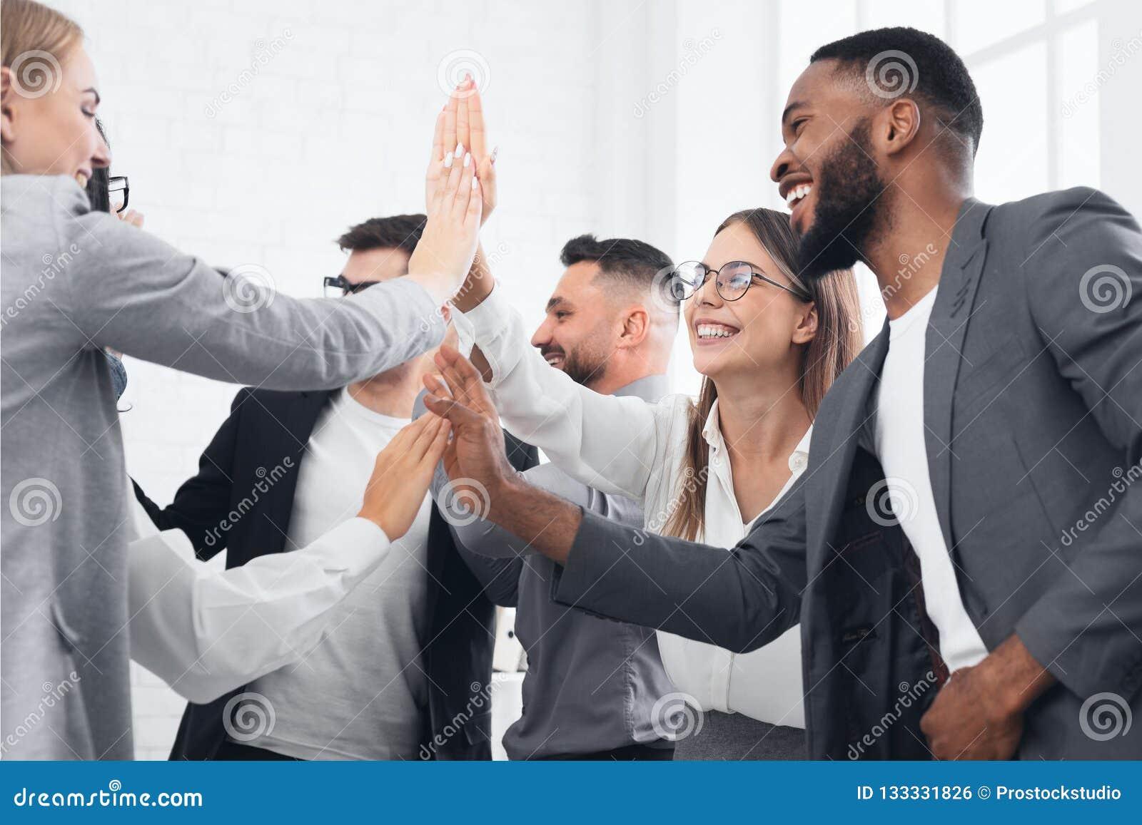 Accomplissement d équipe, hommes d affaires divers donnant haut cinq
