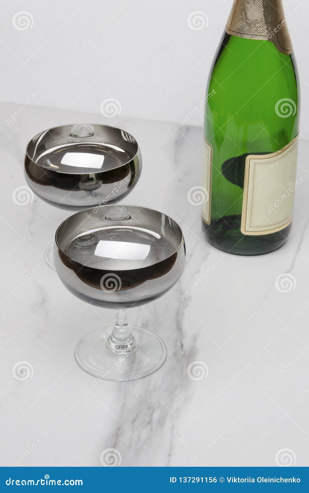 Accoppi dei vetri, bottiglia verde di champagne sulla tavola di marmo