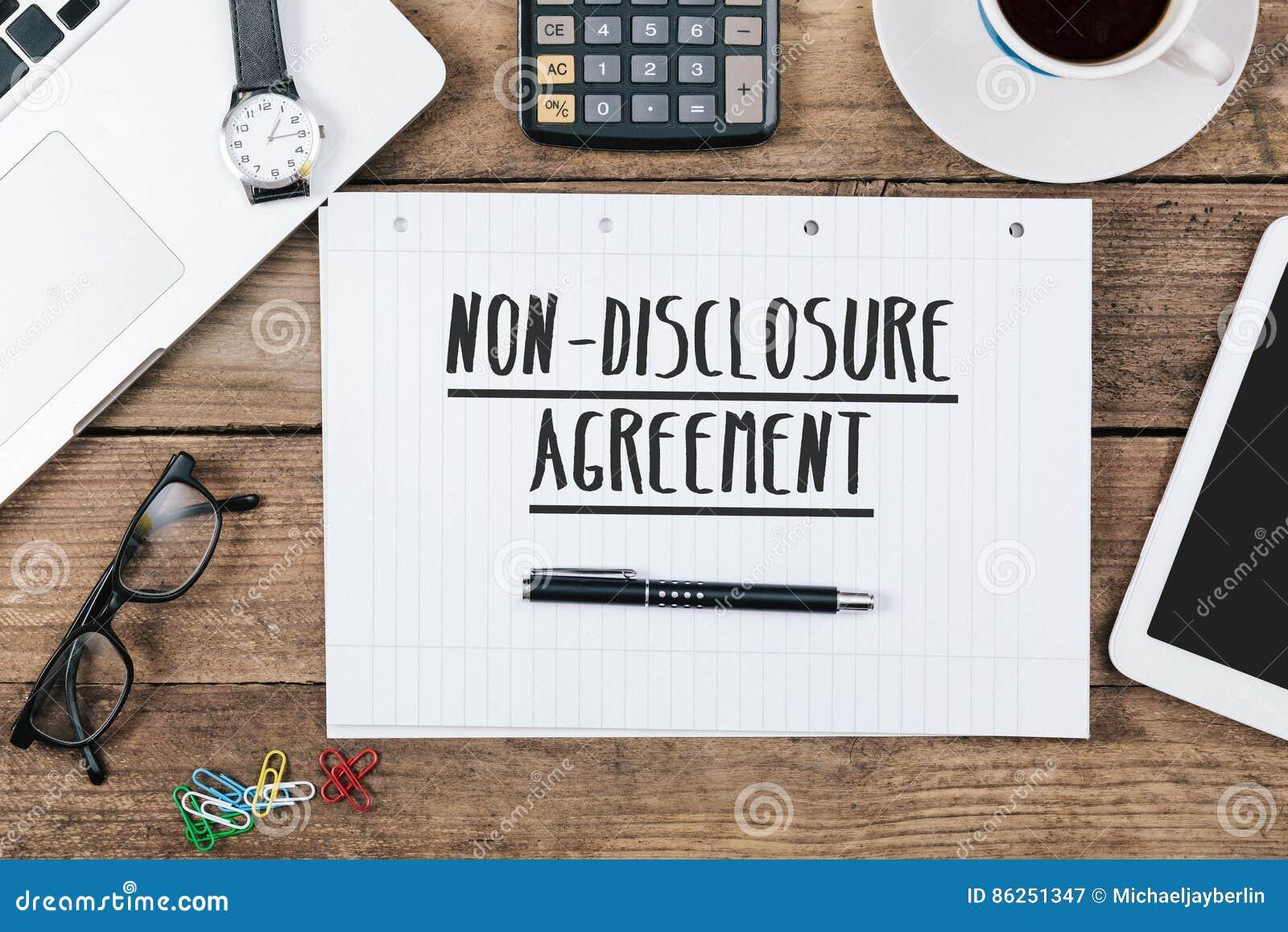 Accordo non-diclosure sul taccuino sulla scrivania con il computer