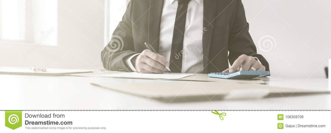 accountant writing notes and working with a manual calculator stock rh dreamstime com Accountant Room Antique Accountants Desk with Glass Top