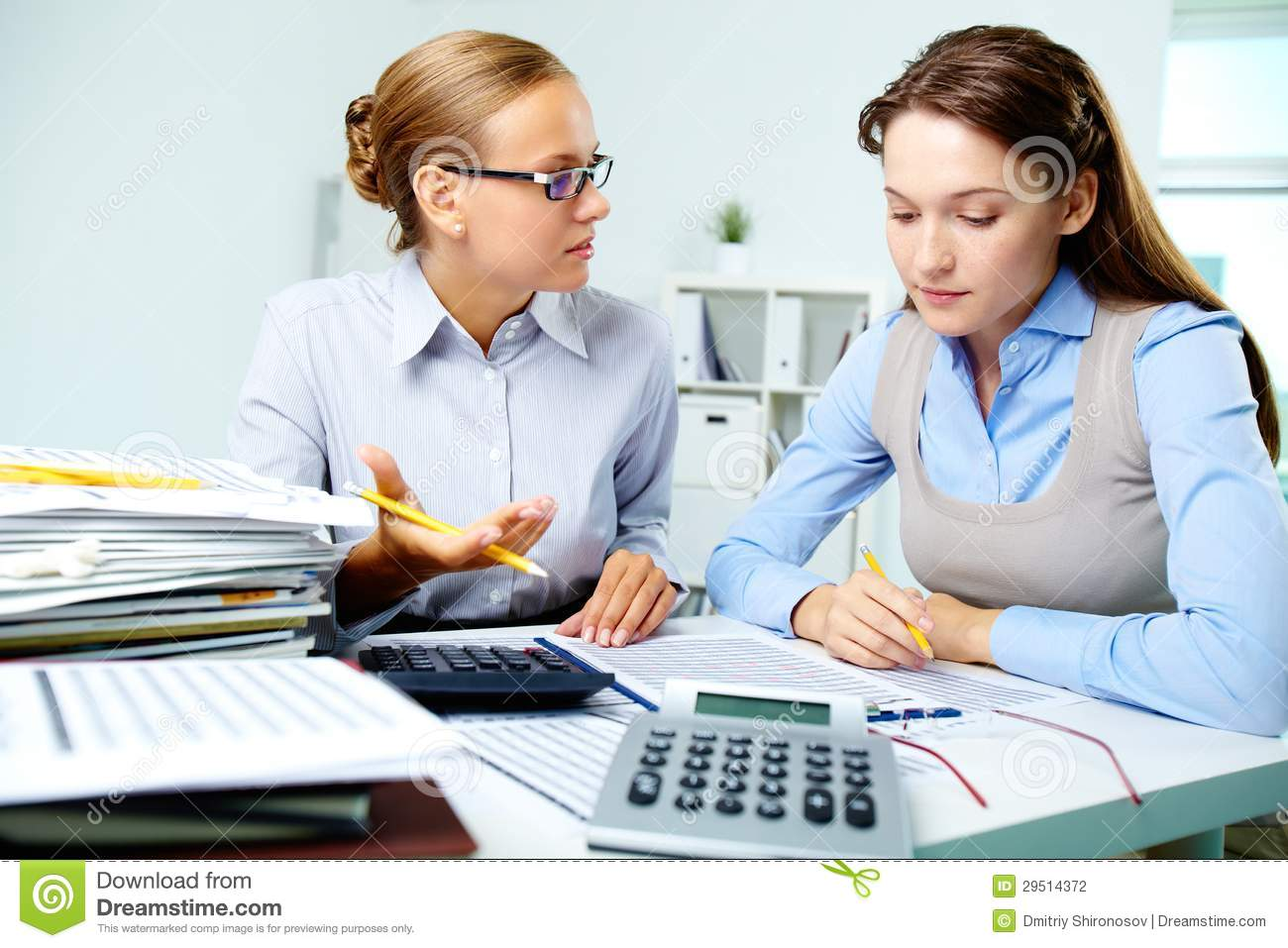Portrait of young businesswomen interacting while working with papers ...