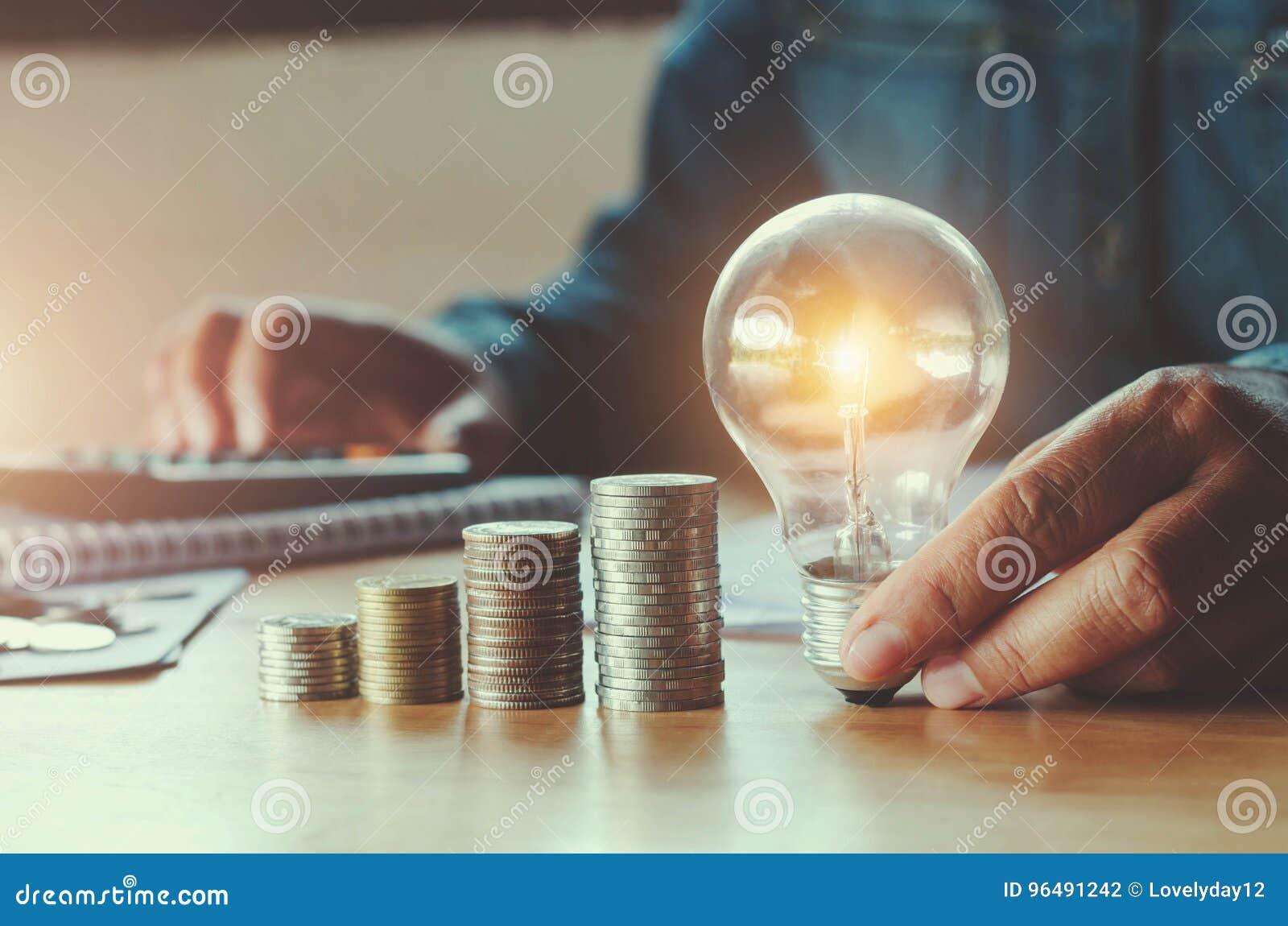Accountin d affaires avec l argent d économie avec la main tenant l ampoule
