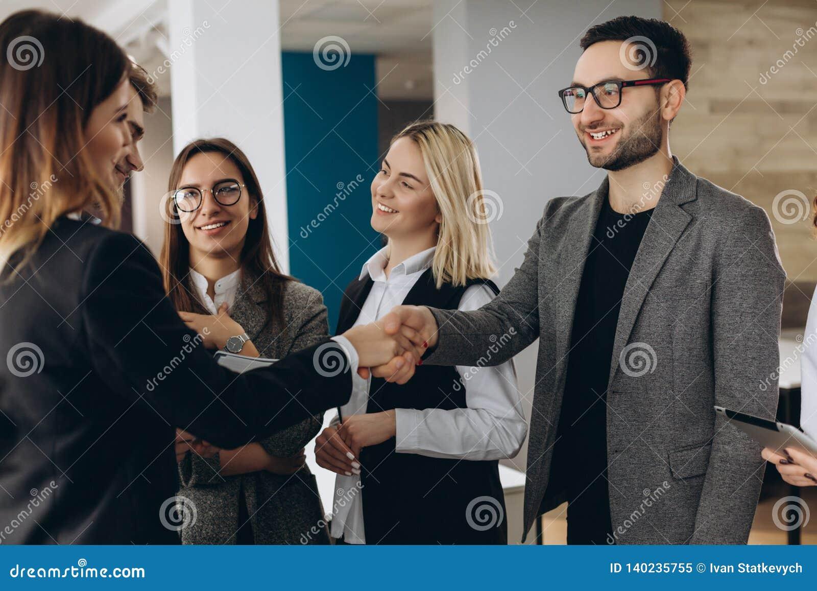 Accueil à notre équipe ! Vue supérieure de jeunes hommes modernes dans la tenue de détente futée se serrant la main tout en trava