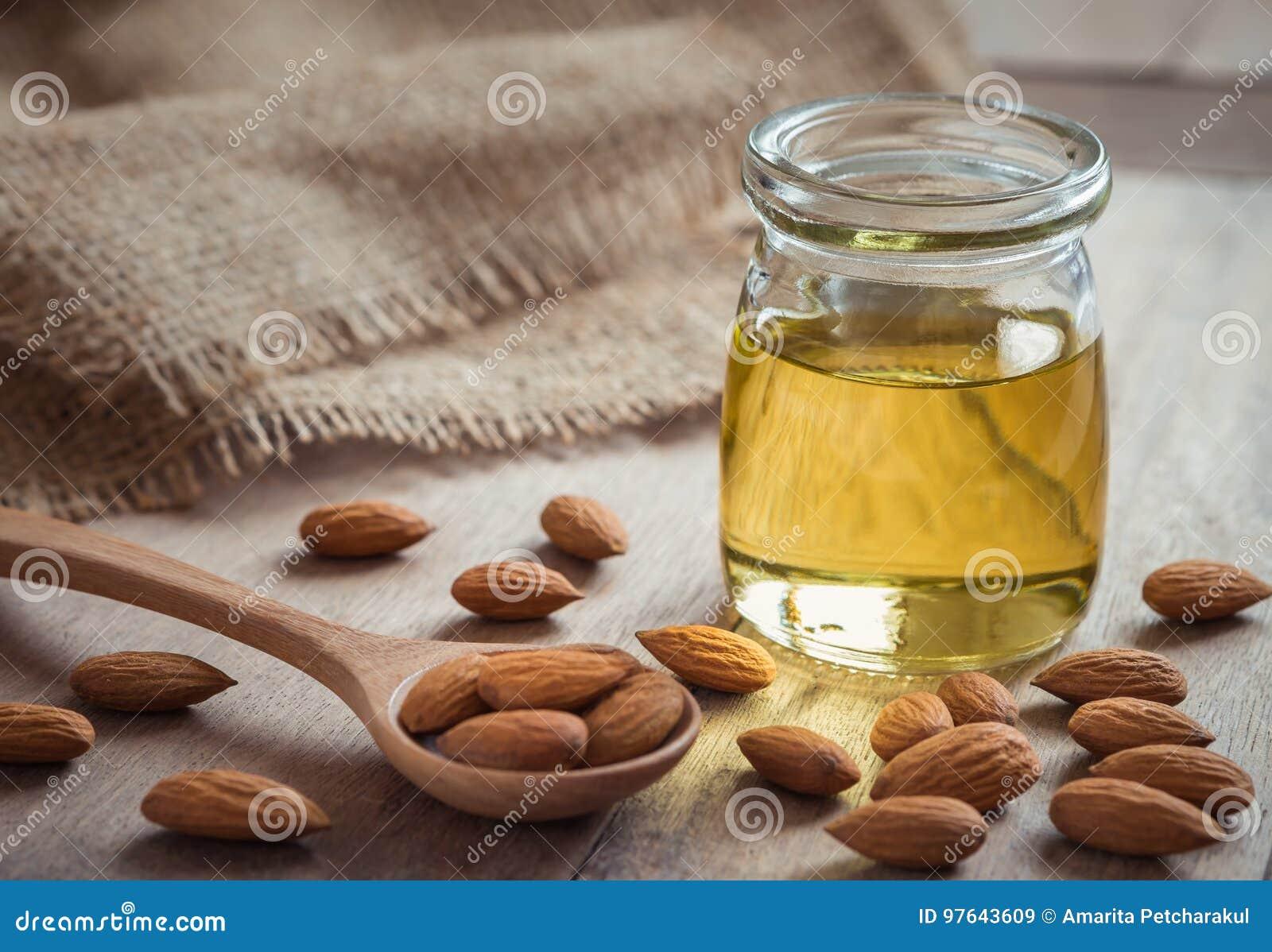 Aceite de almendra en la botella de cristal y almendras en la tabla de madera