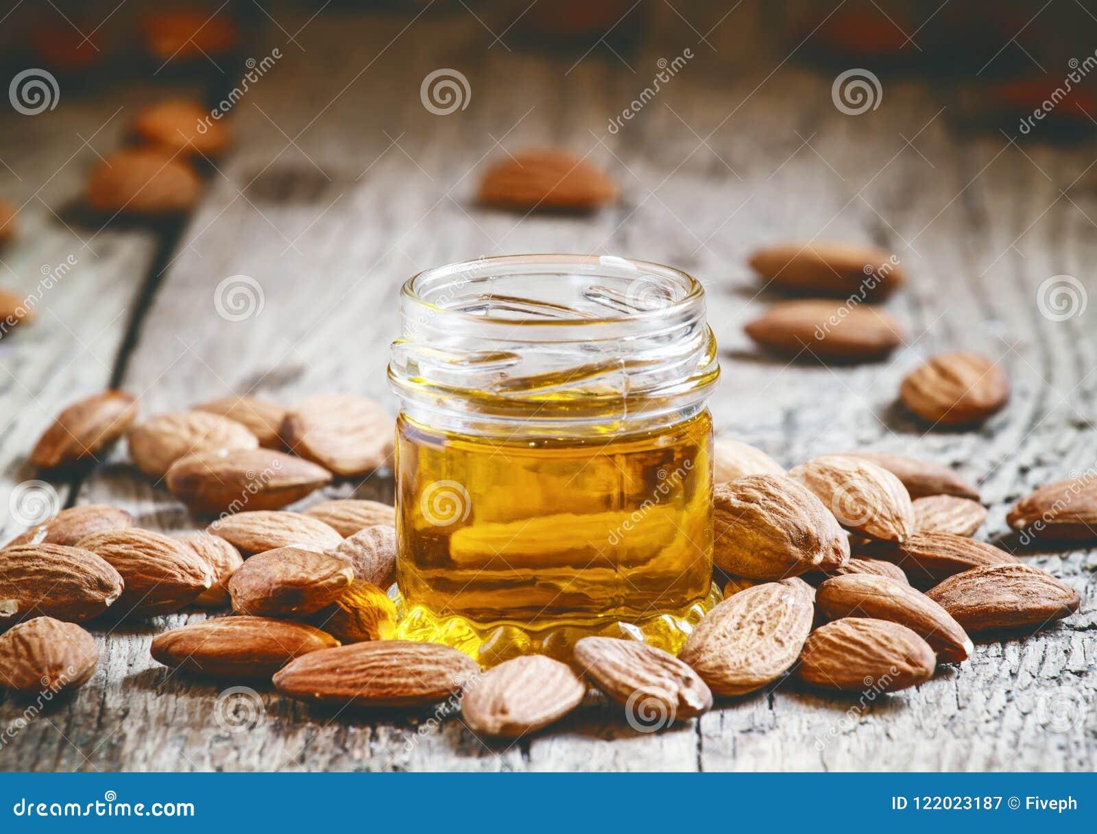 Aceite de almendra en un pequeño tarro de almendras y de nueces en un b de madera viejo