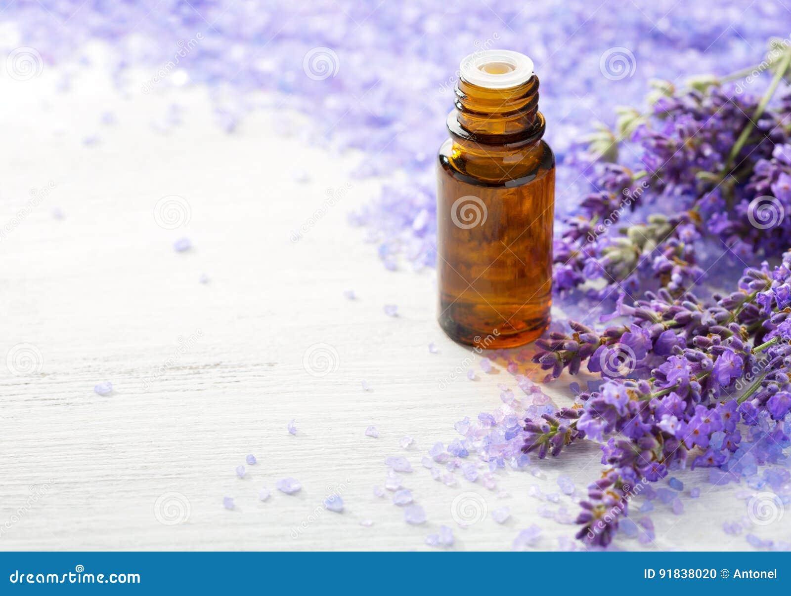 Aceite esencial de la lavanda, puntillas de la lavanda y sales de baño minerales en la tabla de madera Foco selectivo