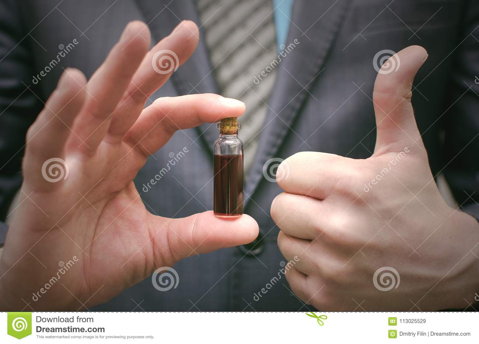 Aceite esencial de la píldora roja en las manos masculinas Presentación del esteroide o de la droga