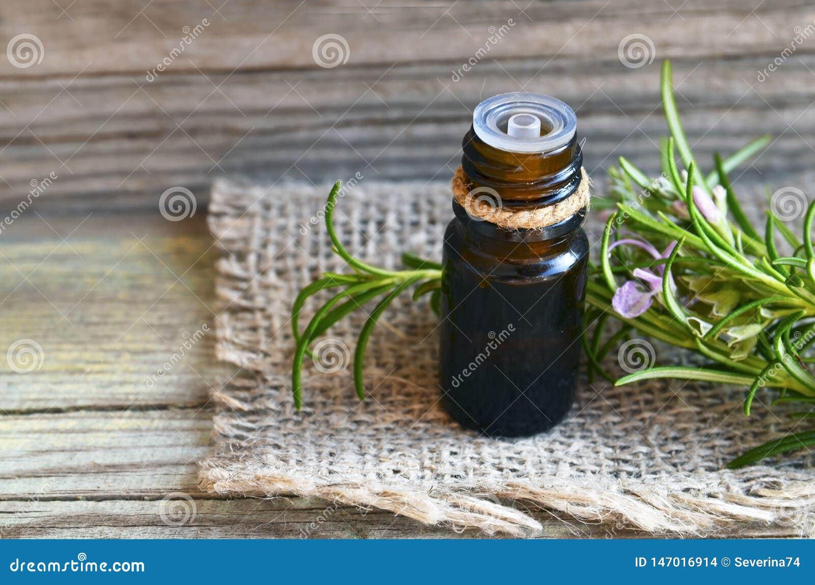 Aceite esencial de Rosemary en una botella de cristal del dropper con la hierba verde fresca del romero en la tabla de madera vie
