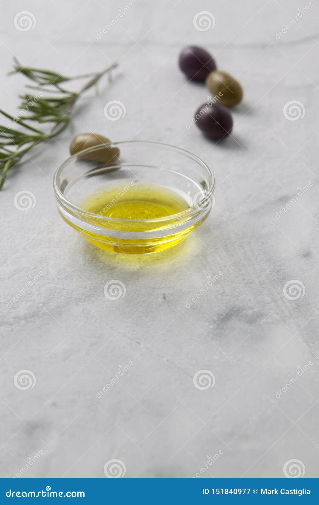 Aceitunas y aceite de oliva con las hierbas en un backgound de mármol con la profundidad del foco limitada