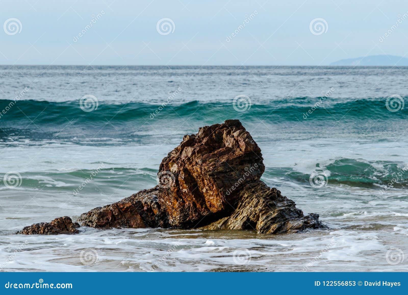 Acene cresting e mover-se para a rocha perto da costa pacífica; espuma no primeiro plano, céu no fundo