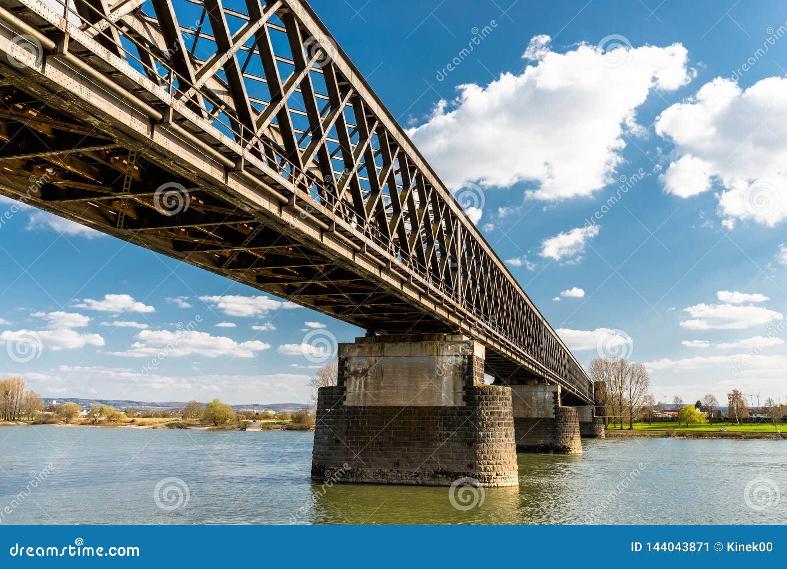 Acero, estructura de enrejado de un puente ferroviario sobre un río con un fondo del cielo azul con las nubes blancas en Alemania
