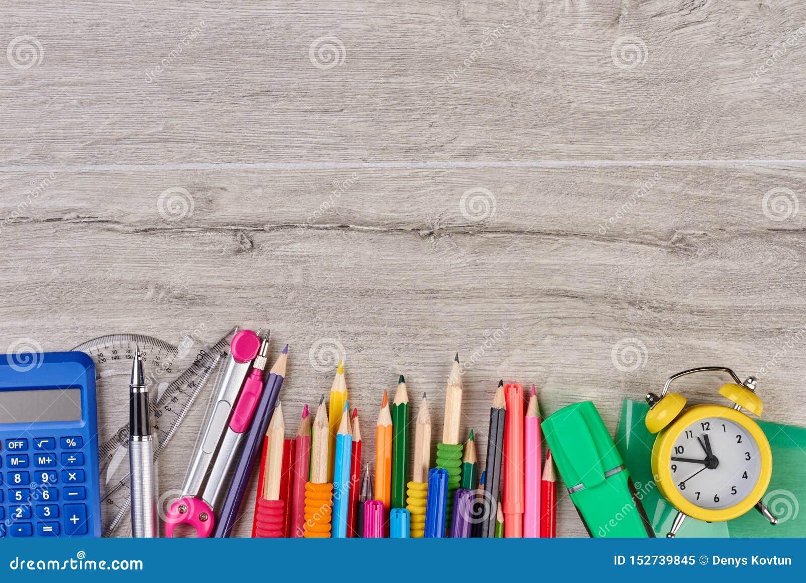 Acessórios da escola no fundo de madeira cinzento
