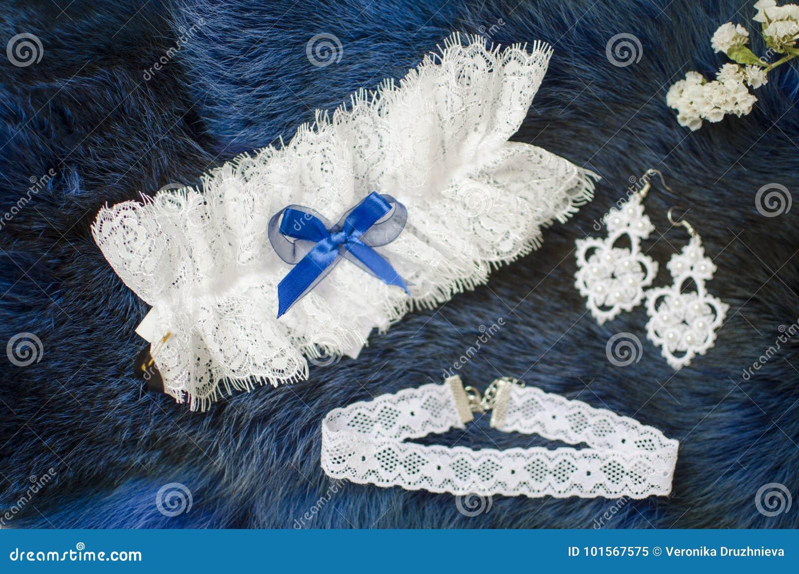 a0a81d2bb Acessórios nupciais do laço branco no fundo do azul da pele Liga do  casamento no fundo da textura brincos nupciais da forma