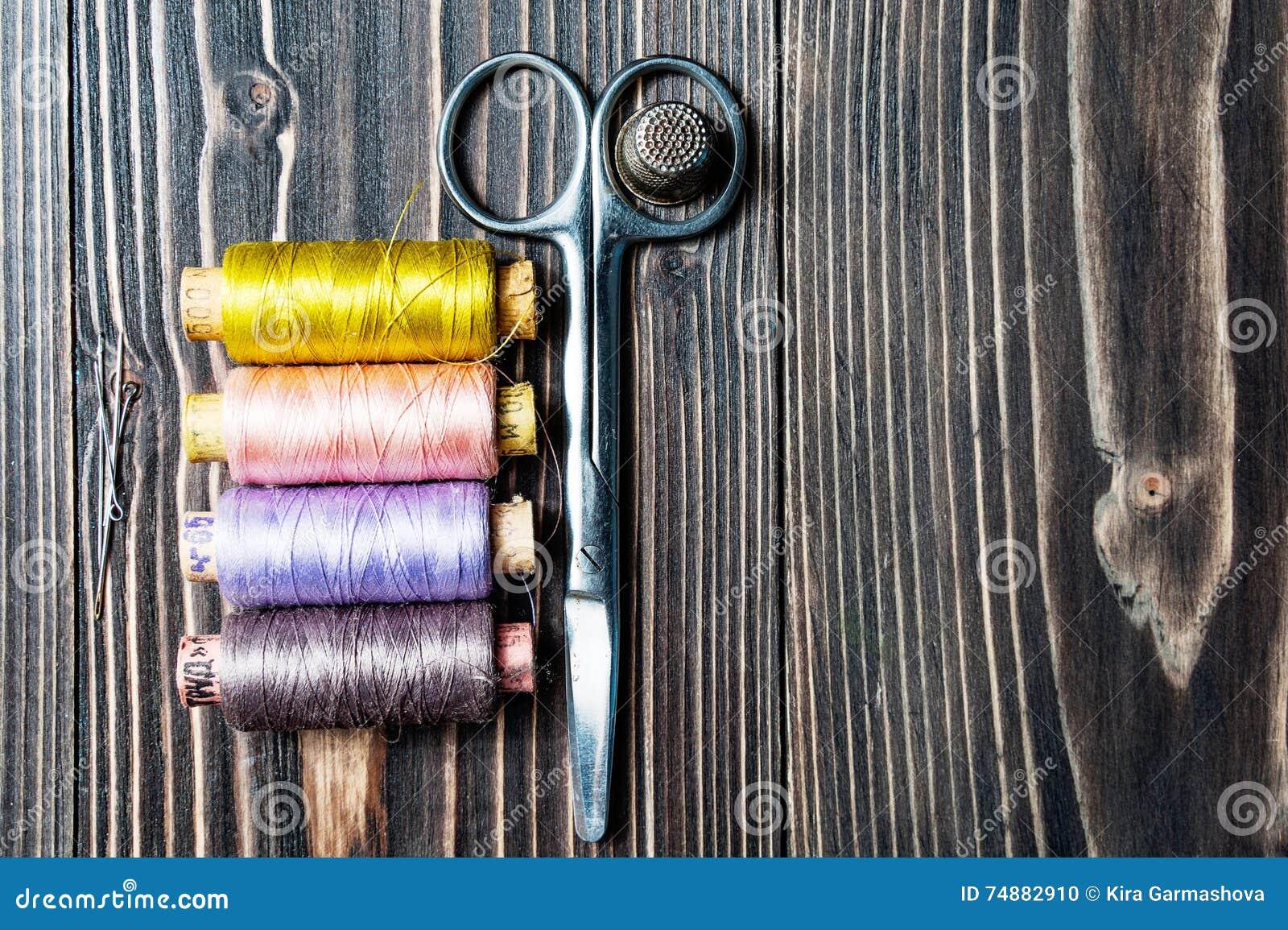 Acessórios para costurar na tabela de madeira escura