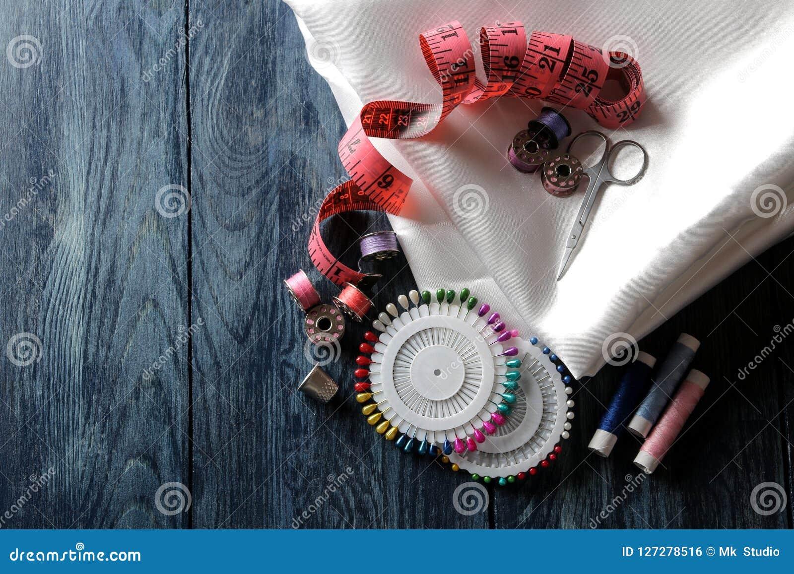 Acessórios para linhas costurar e de bordado, tela, tesouras, bobinas, pinos, centímetro em uma obscuridade - fundo de madeira az