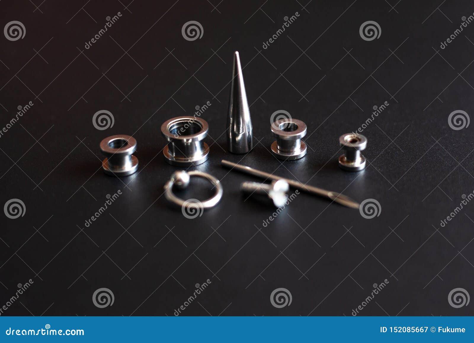 Acessórios perfurando em uma joia inoxidável do metal do fundo preto para amantes da punctura