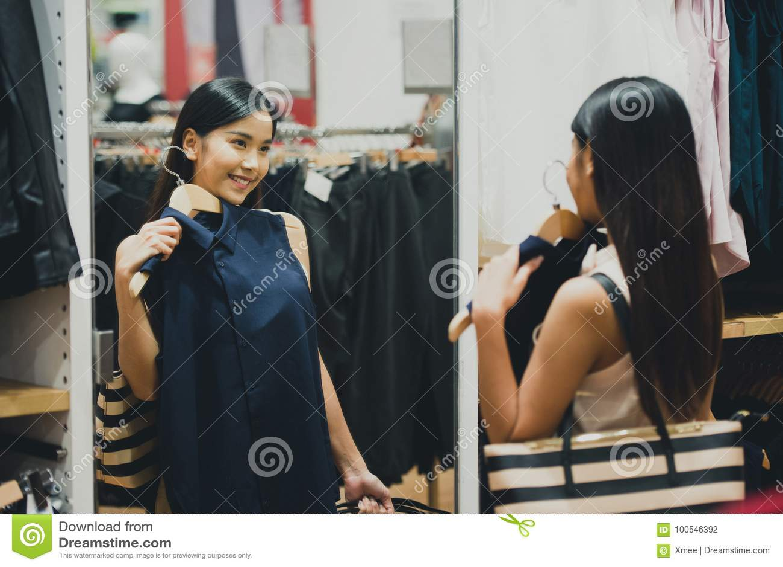 Achats de femme choisissant des robes regardant dans le miroir incertain