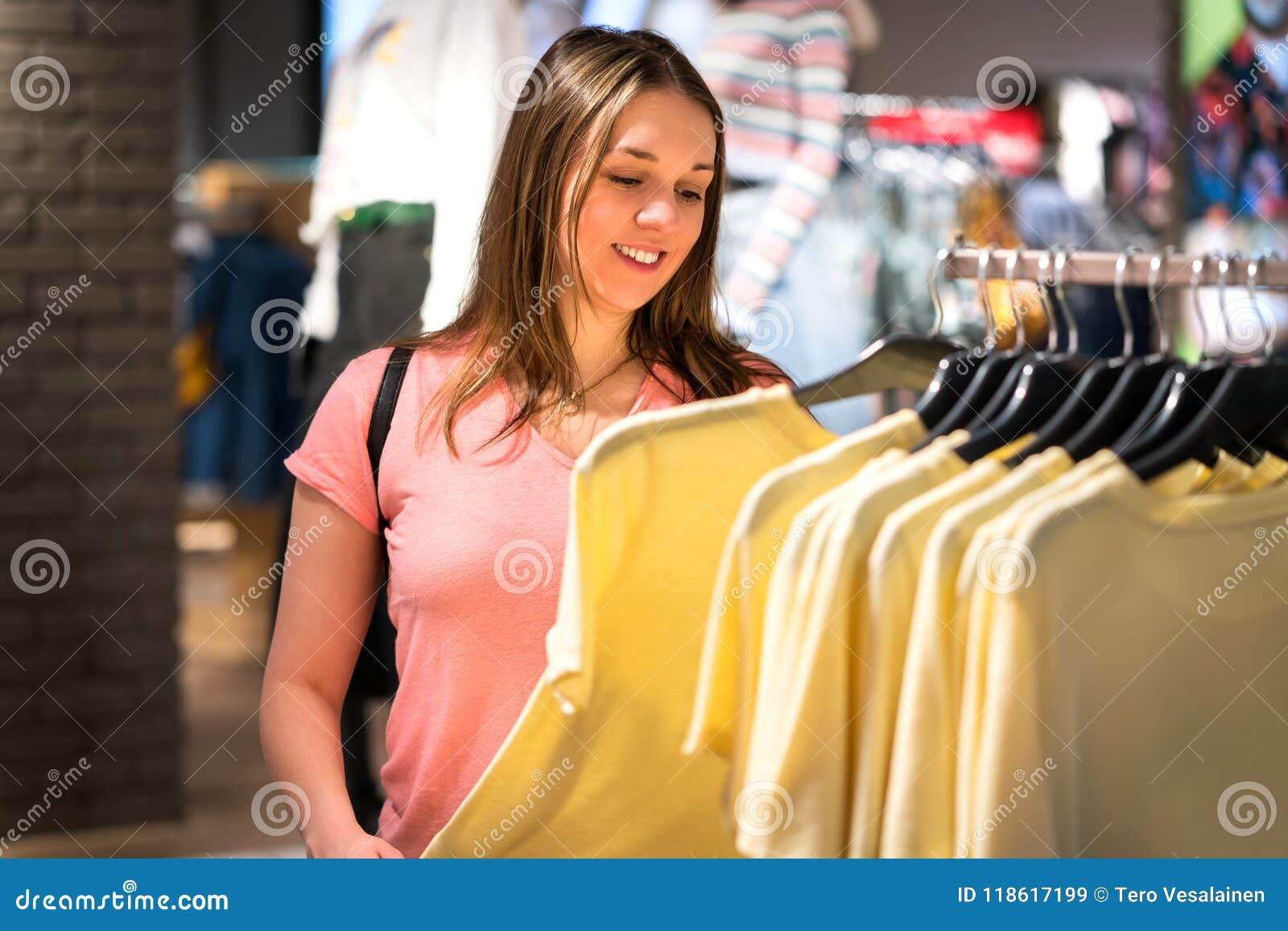 Achats de femme dans le magasin de mode pendant la vente et le dégagement