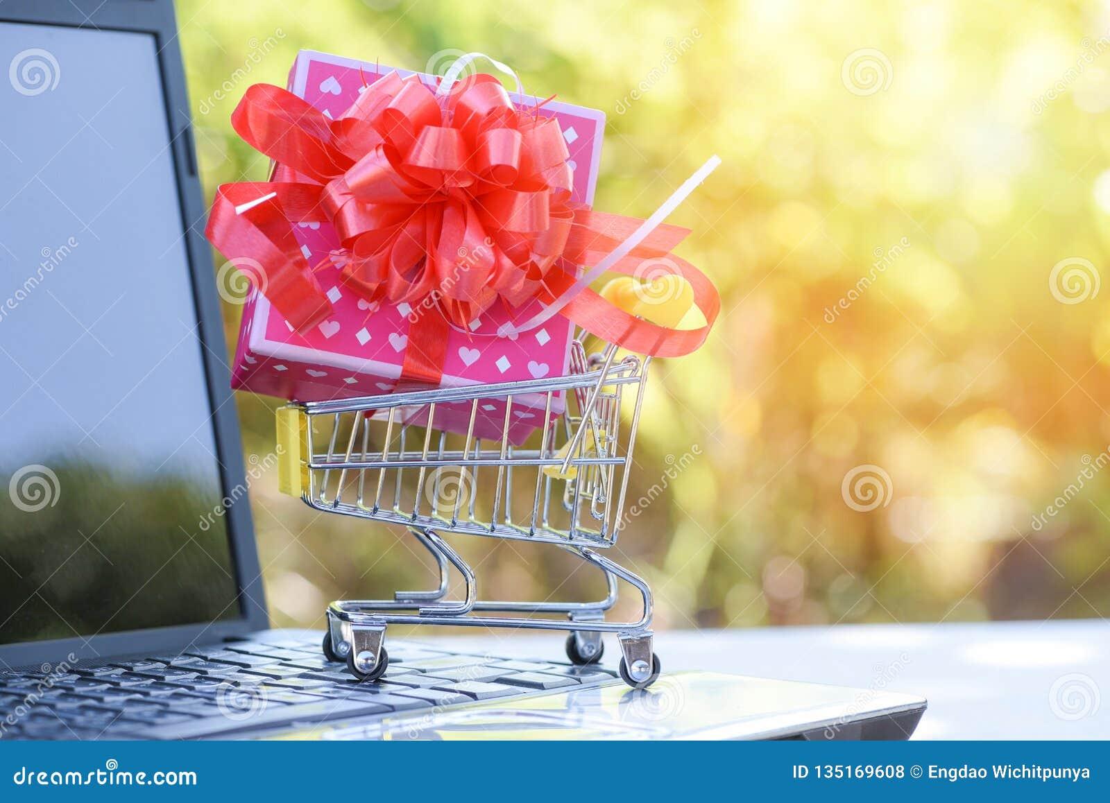 Achats de jour de valentines et boîte actuelle de rose de boîte-cadeau avec l arc rouge de ruban sur le caddie faisant des emplet
