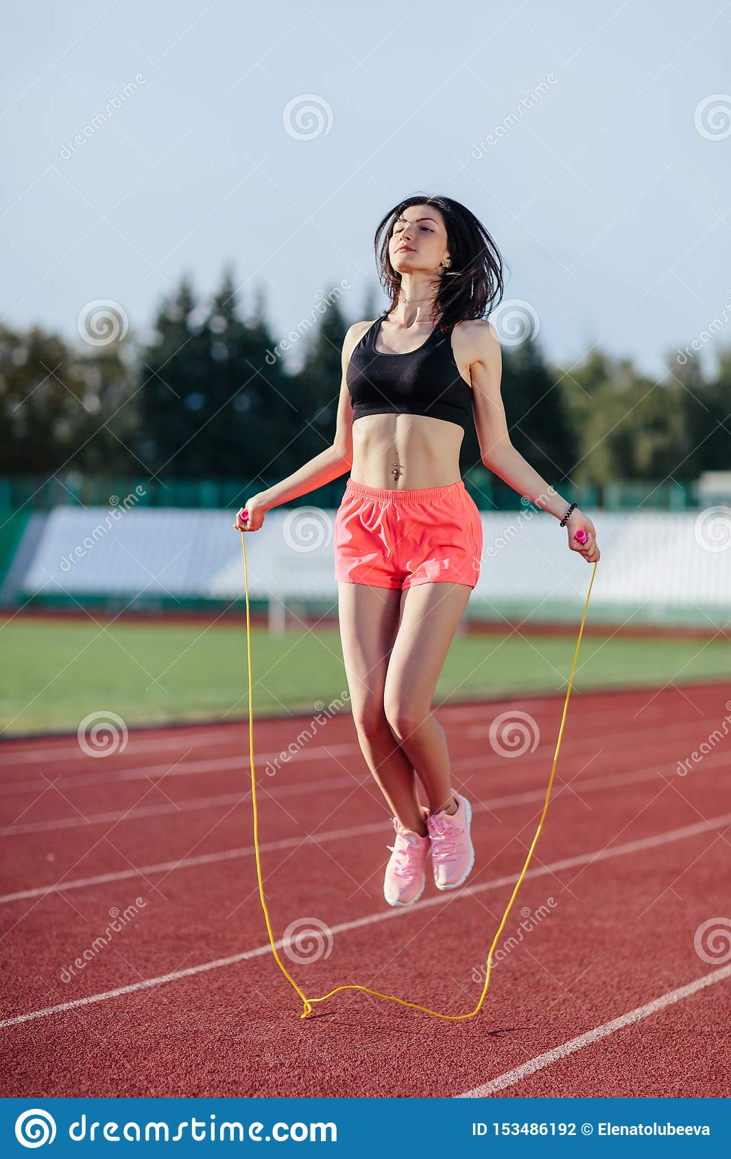 Achieving best results. Beautiful young brunette woman in sports clothing skipping rope and smiling while exercising on the