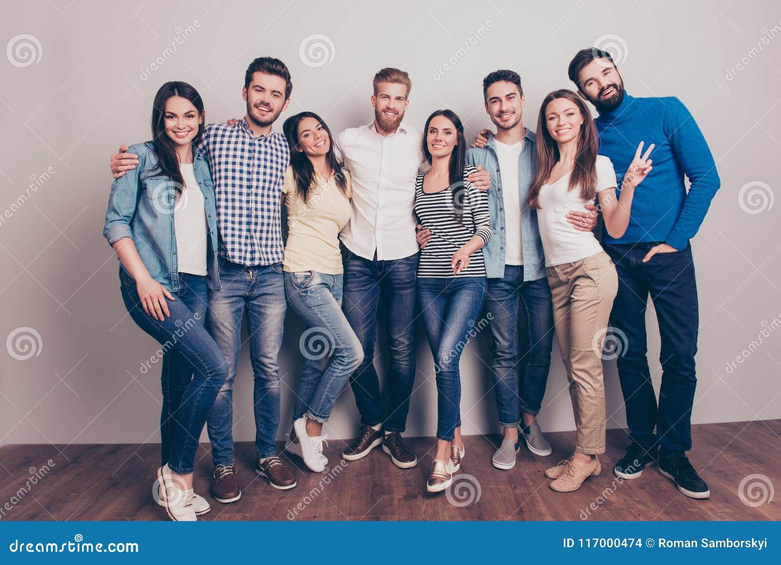 Acht glückliche Freunde werfen nahe der Wand, dem Lächeln und dem gestur auf