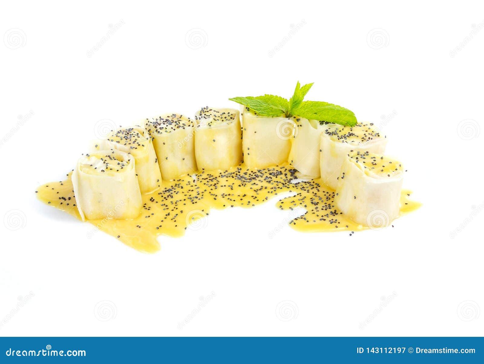 Acht stukken sushi zoals cakes met van de vanillebovenste laagje en papaver zaden die op witte achtergrond worden geïsoleerd
