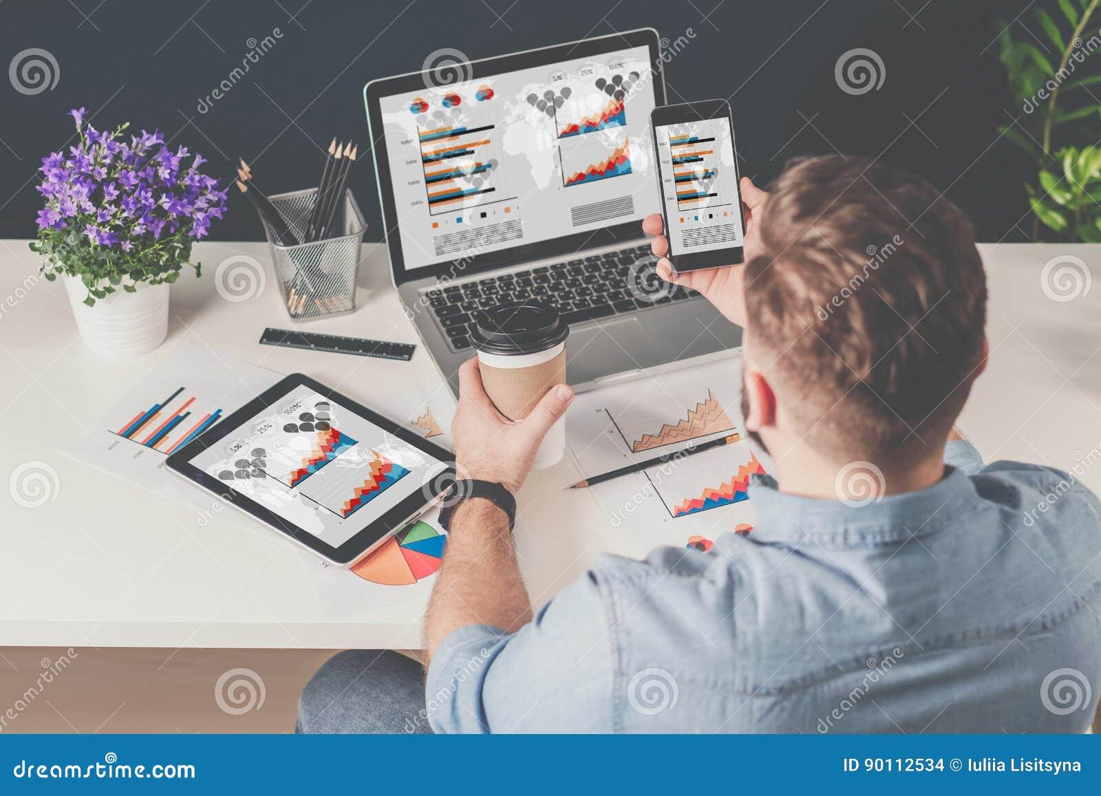 Achter mening De jonge gebaarde zakenman in denimoverhemd zit in bureau bij lijst en gebruikt smartphone met grafieken, diagramme