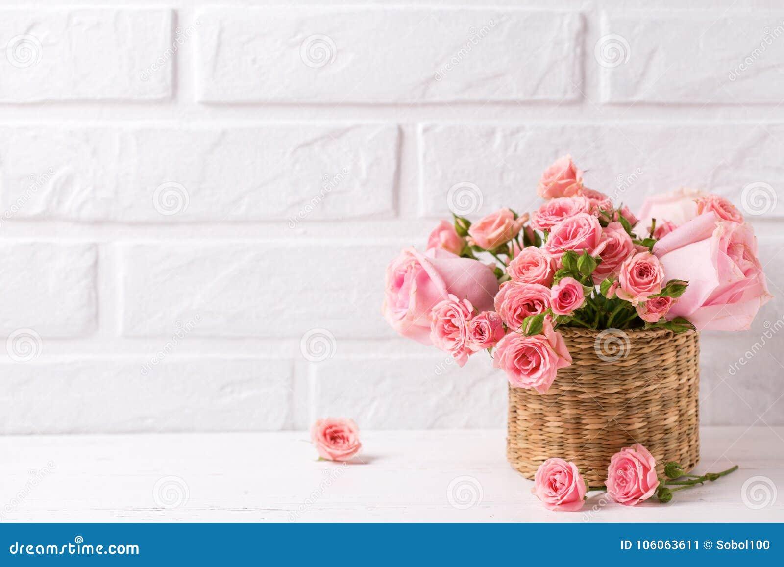 Achtergrond met roze rozenbloemen tegen witte bakstenen muur