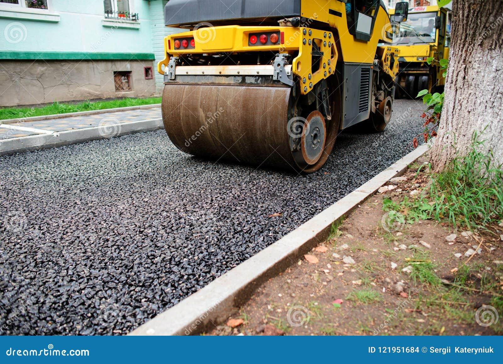 Achtergrond van asfaltrol dat stapelt en heet asfalt drukt De machine van de wegreparatie