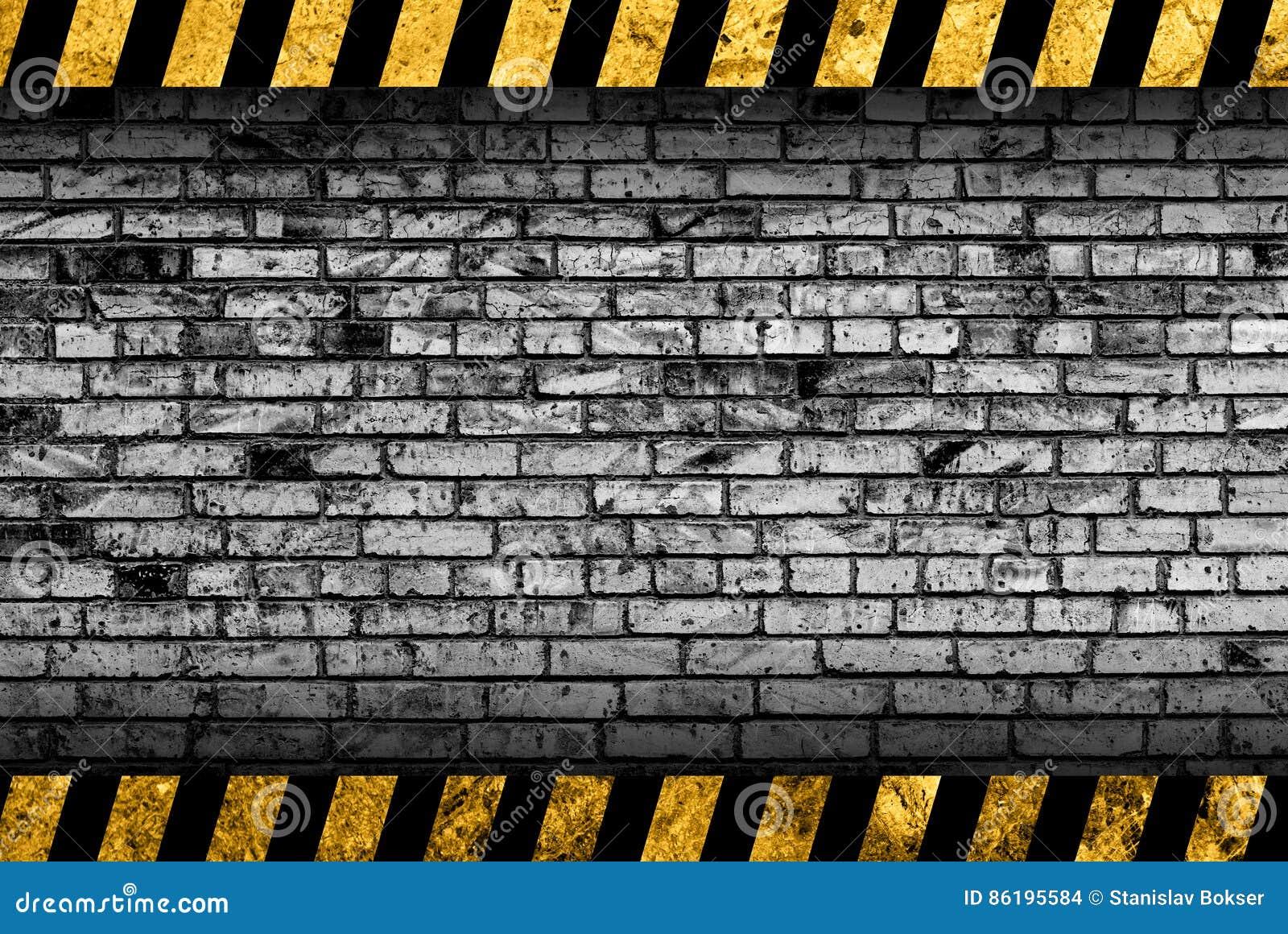 Achtergrond van de Grunge de grijze bakstenen muur met waarschuwingsstrepen