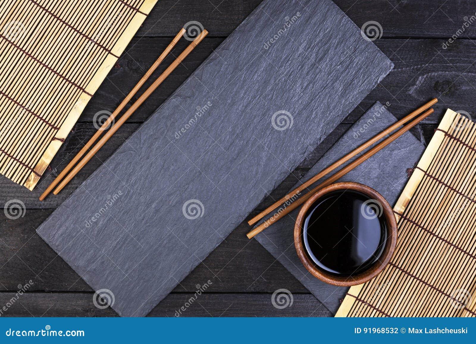 Achtergrond voor sushi Bamboemat, sojasaus, eetstokjes op donkere lijst