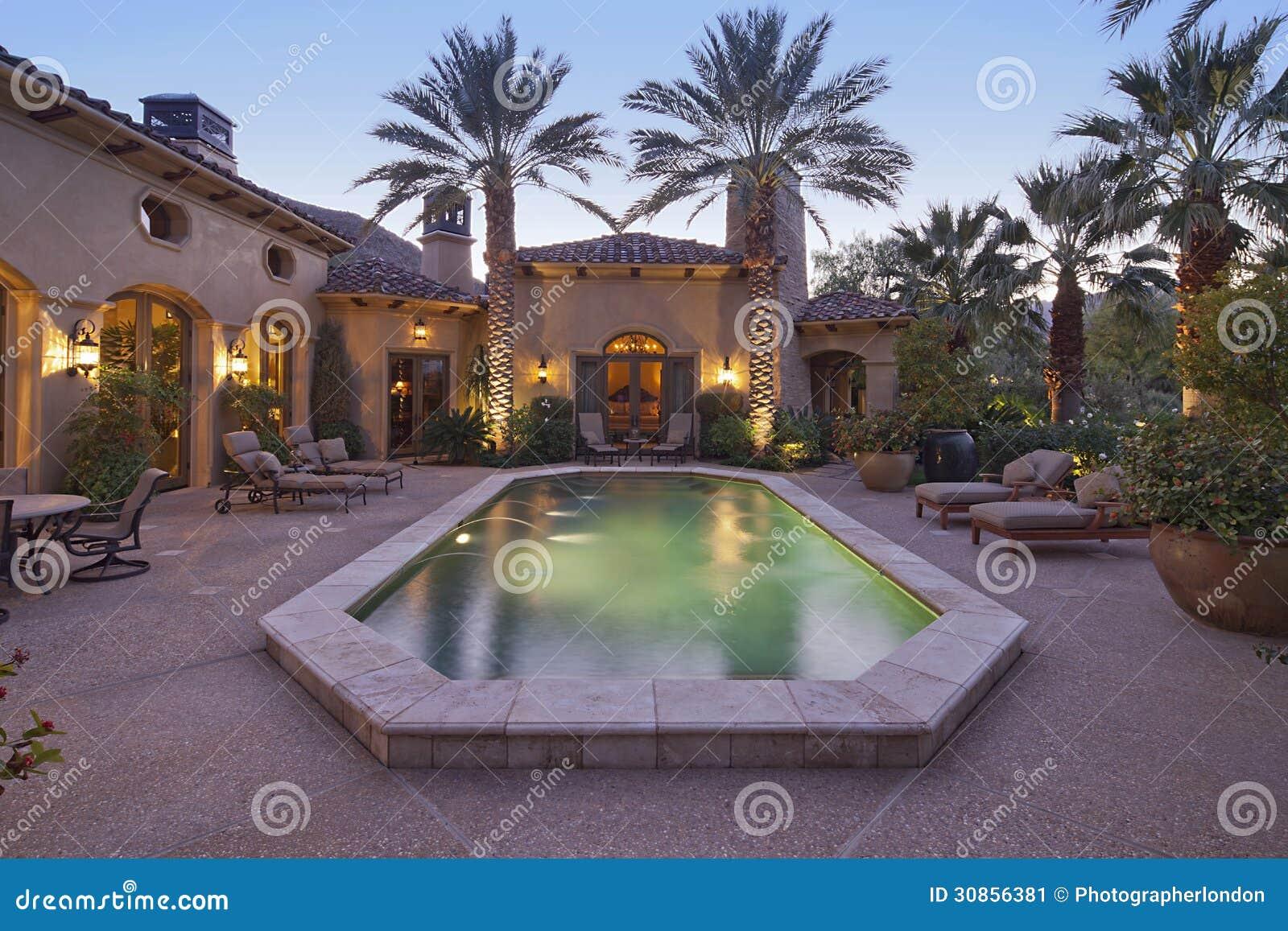 Achteringang van luxevilla bij nacht met zwembad