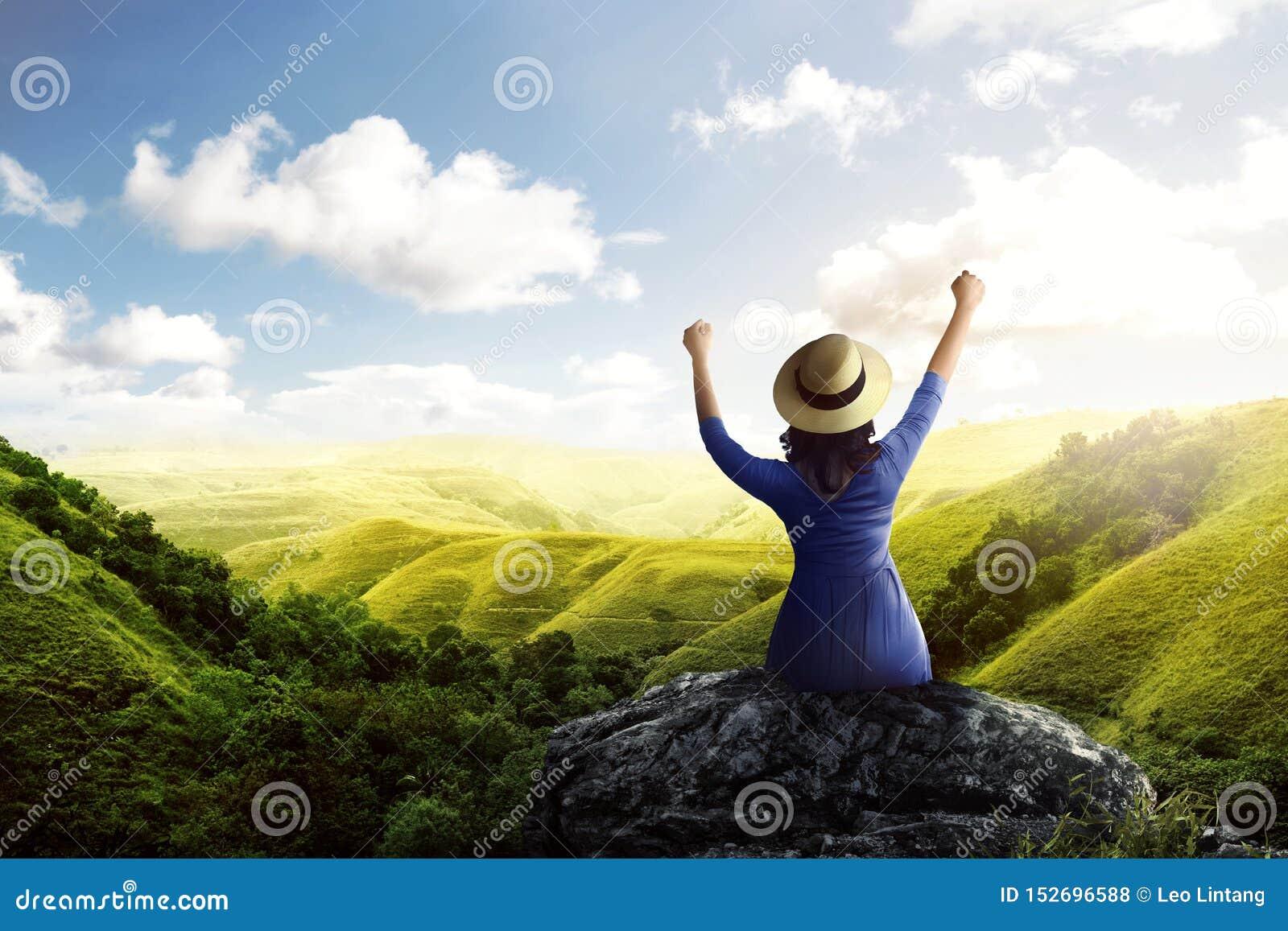 Achtermening van Aziatische vrouw in hoedenzitting op de rots en het bekijken groene meningen