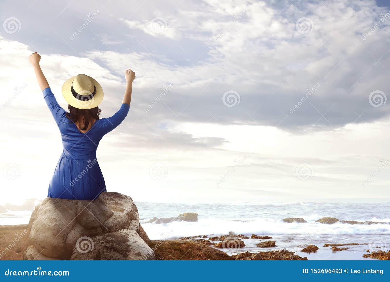 Achtermening van Aziatische vrouw in hoedenzitting op de rots en het bekijken de oceaanmening