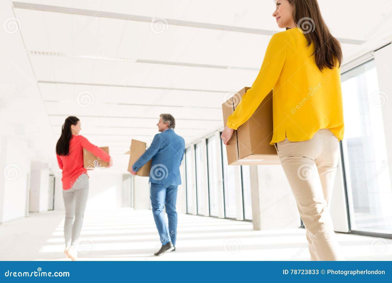 Achtermening van bedrijfsmensen met kartondozen die zich in nieuw bureau bewegen